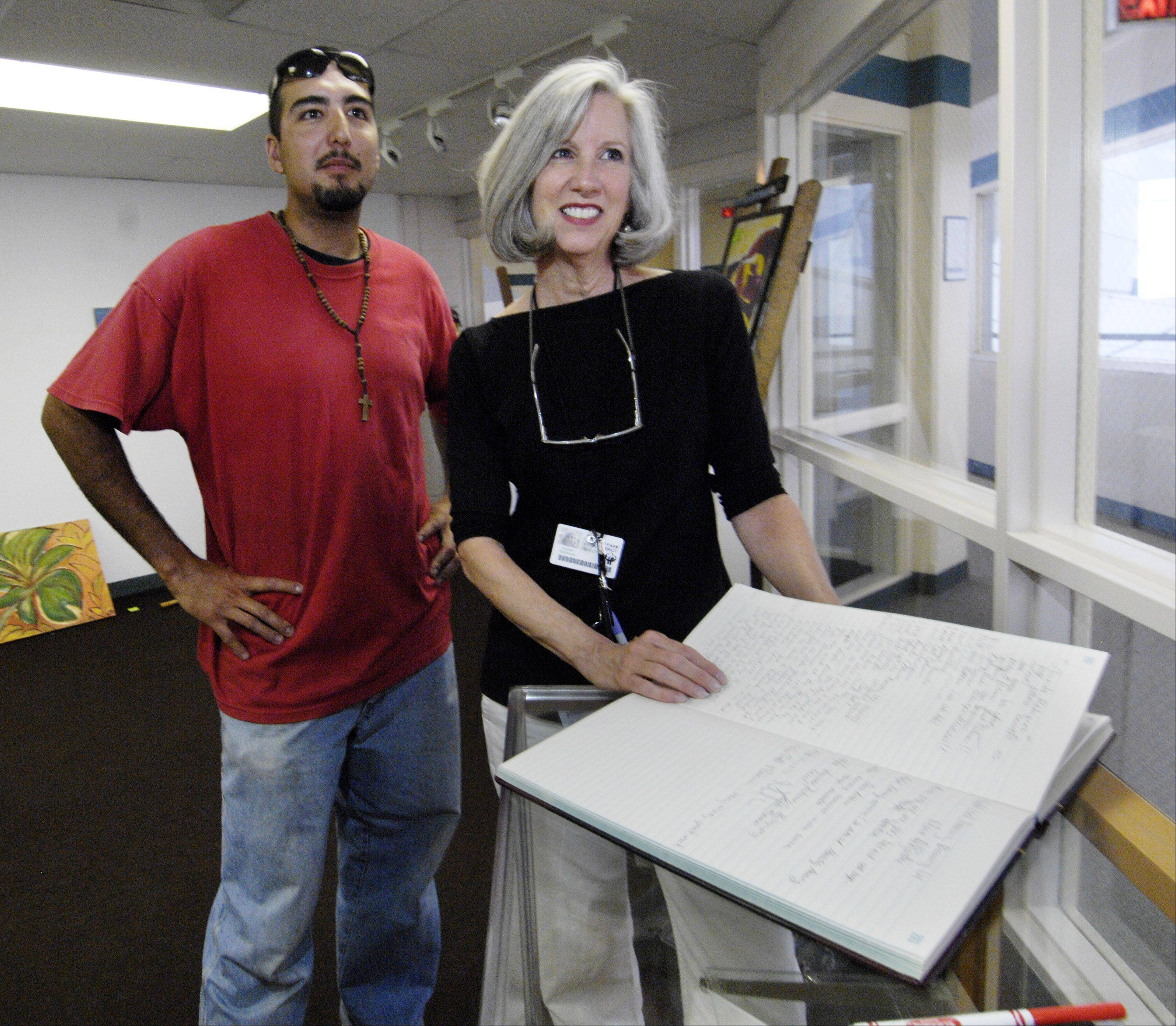 Self-taught artist and tree-trimmer Raul Maldonado of Hanover Park and curator Susan Matthews, arts coordinator for the Hanover Park Park District, look through guests' comments from Maldonado's first art show at the community gallery.
