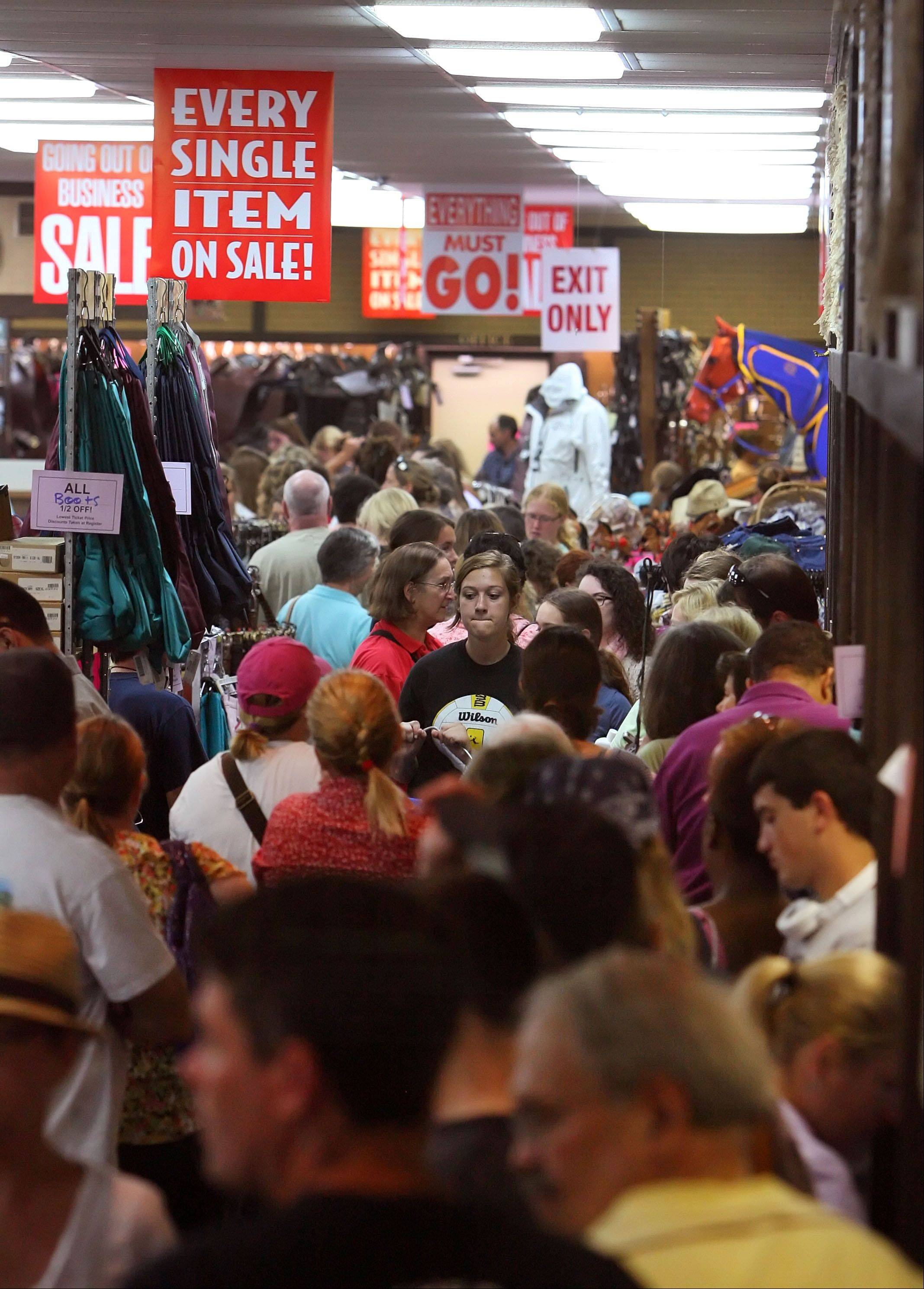 Hundreds wait in line to pay Thursday during a liquidation sale at the Saddle Shop in Libertyville.
