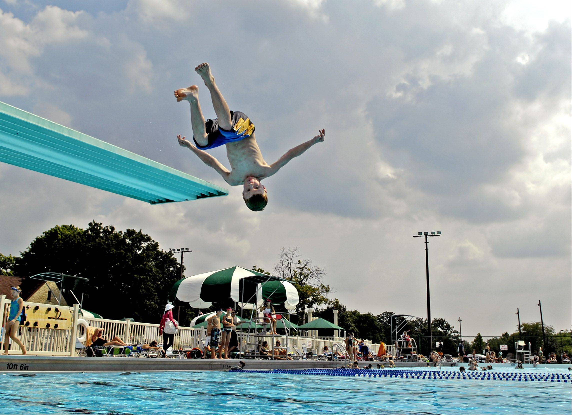 Ryan Summerwill, 9, of St. Charles does a flip off the diving board while enjoying summer at Pottawatomie Pool in St. Charles.