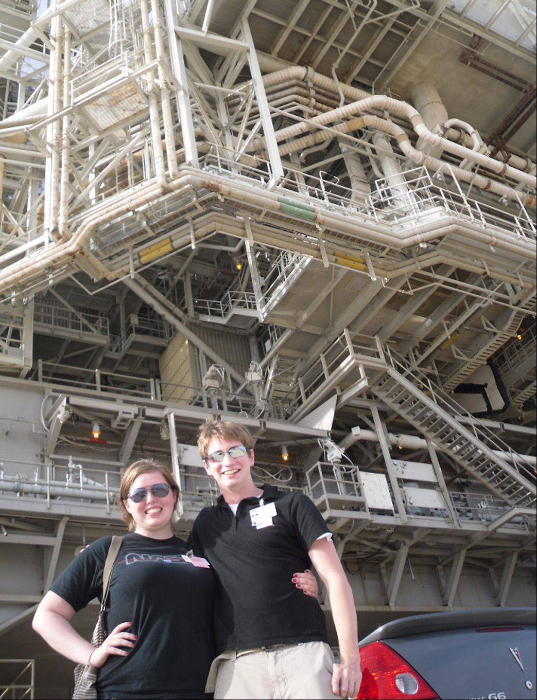 Carthage students Amber Bakkum and Steven Mathe stand below the Mobile Launch Platform at the base of Launchpad 39-A, where shuttle Atlantis sits 48 hours before its scheduled launch.
