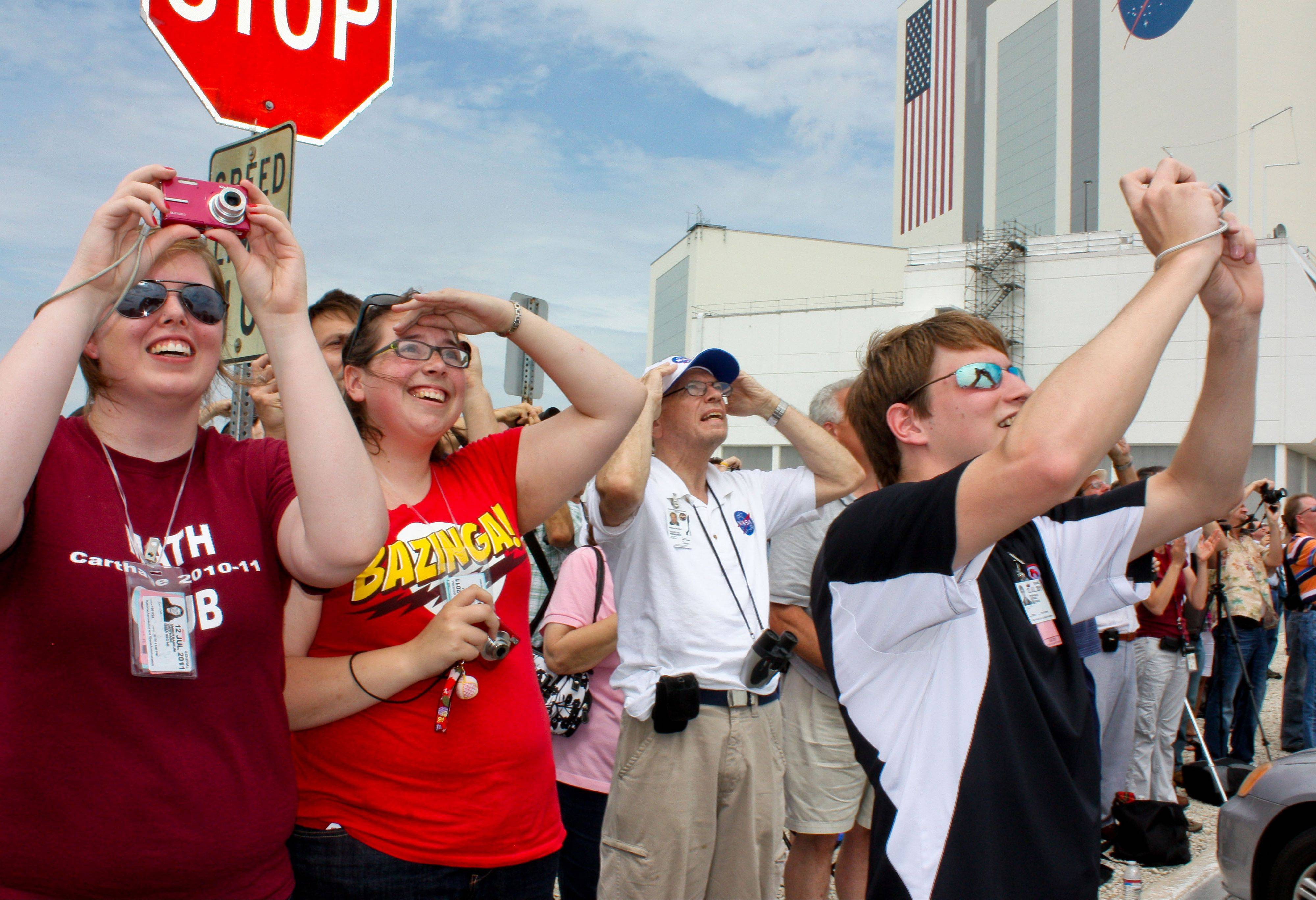 Amber Bakkum of Winthrop Harbor, left, Kimberly Schultz and Steven Mathe of Wauconda watch the final shuttle launch Friday from the Kennedy Space Center, just outside the Launch Control Center.