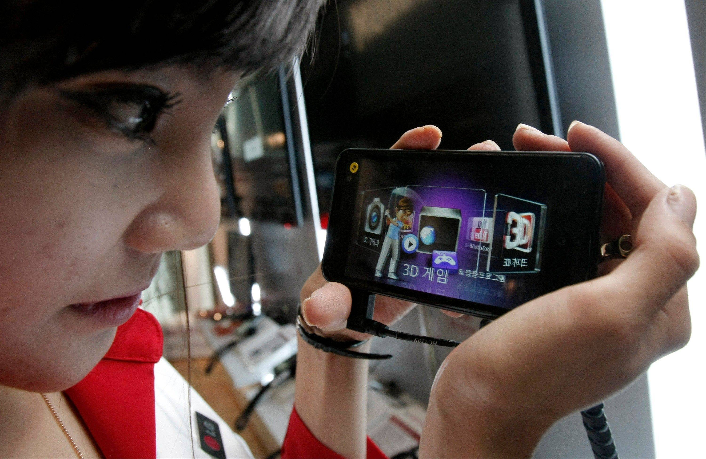 A model looks at a LG Electronics� Optimus 3D phone during a news conference Thursday in Seoul, South Korea. LG Electronics is touting 3D smartphones as an alternative to dedicated handheld game devices.