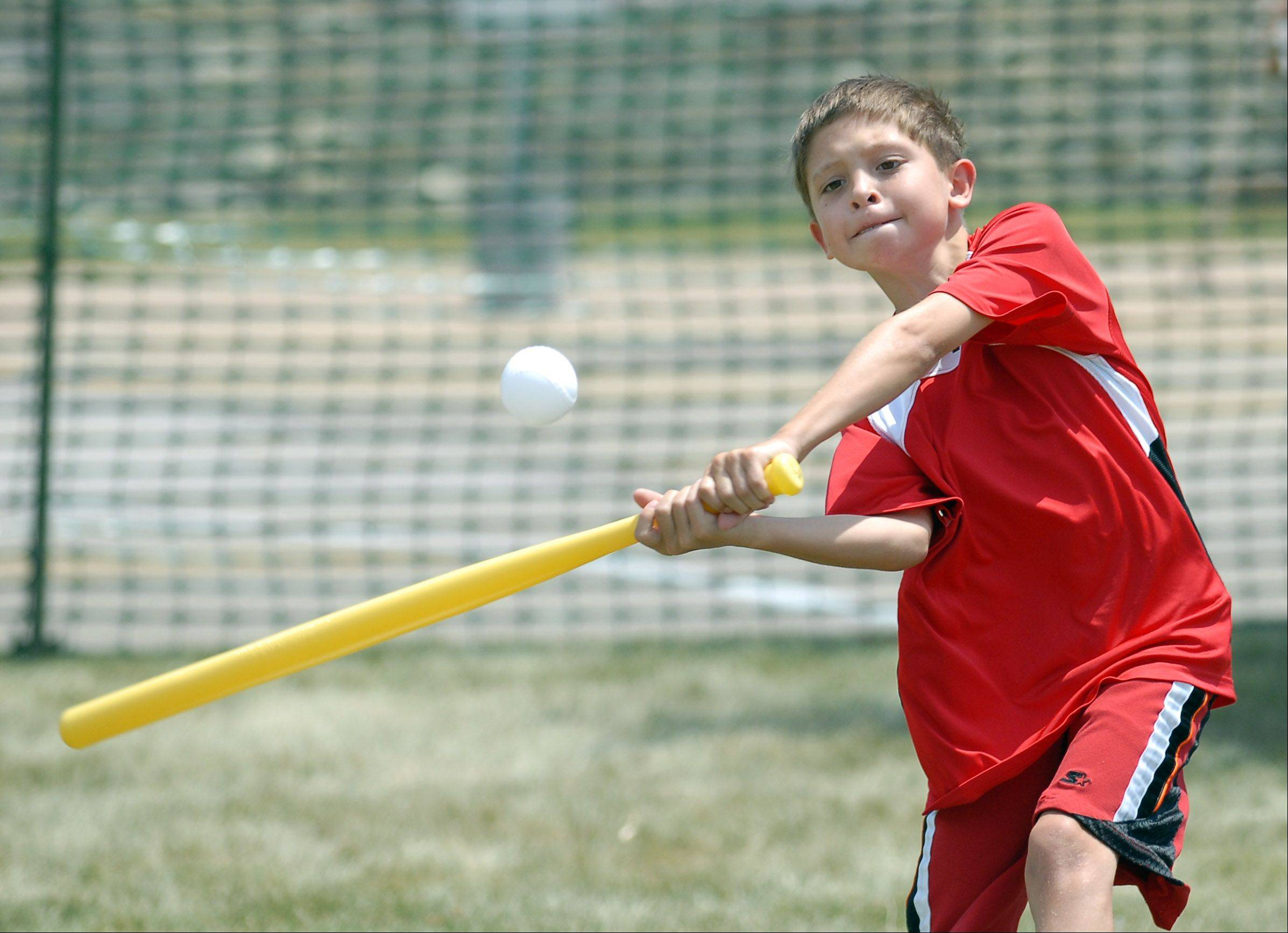 Gerald Manzella, 10, of St. Charles swings for a home run during the Wiffle ball tournament Saturday at Batavia�s Windmill City Festival.