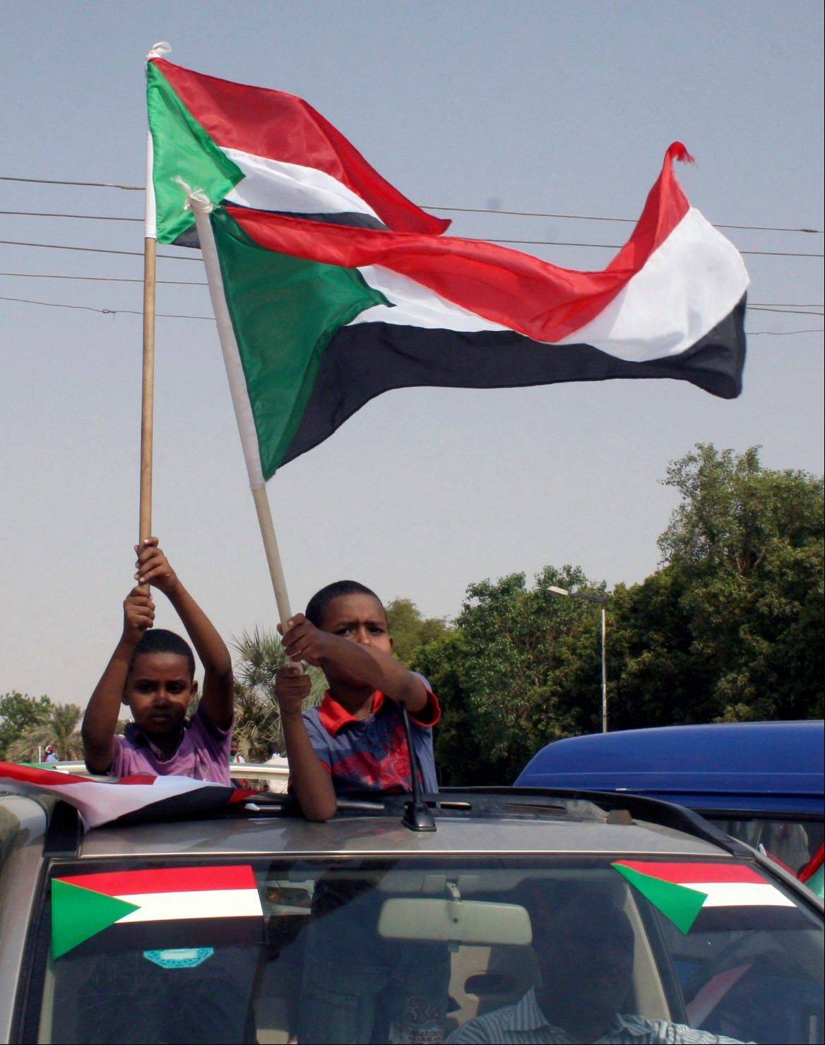 Sudanese boys wave the national flag Saturday during a celebration of Sudan�s separation from South Sudan in the Sudanese capital of Khartoum. South Sudan raised the flag of its new nation for the first time Saturday.