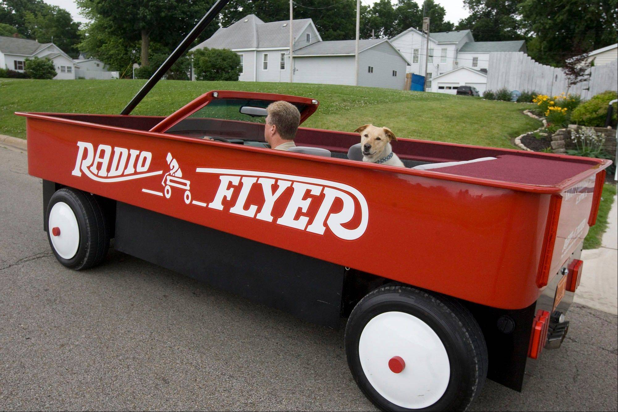 Rick Sullivan of Clinton, Ill., and his dog, Murray, enjoy a ride in a vehicle he created in the shape of a giant Radio Flyer wagon.