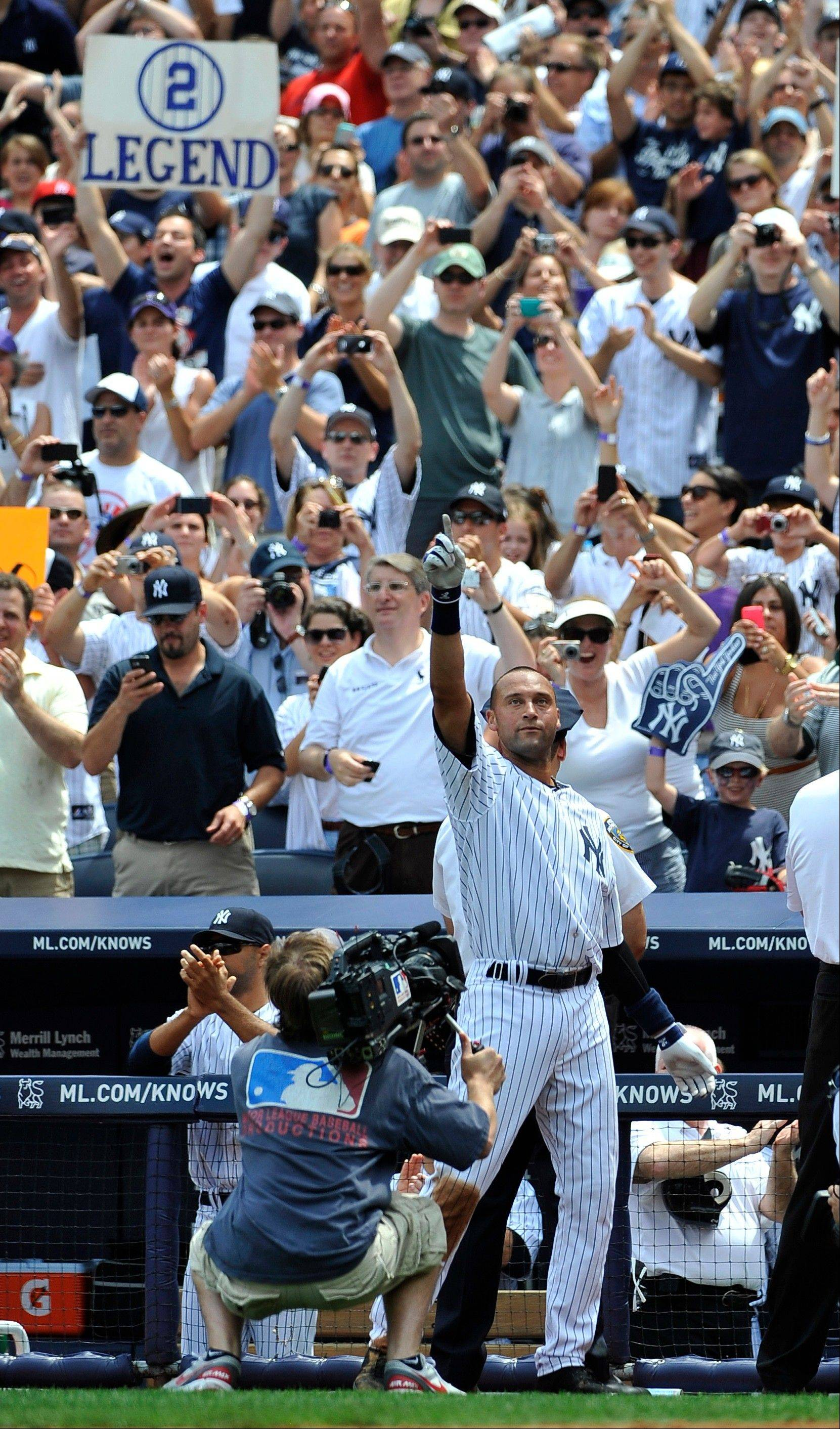 The Yankees' Derek Jeter waves to the cheers of the crowd after he collected his 3,000th hit, a solo home run in the third inning Saturday. Jeter went 5-for-5.