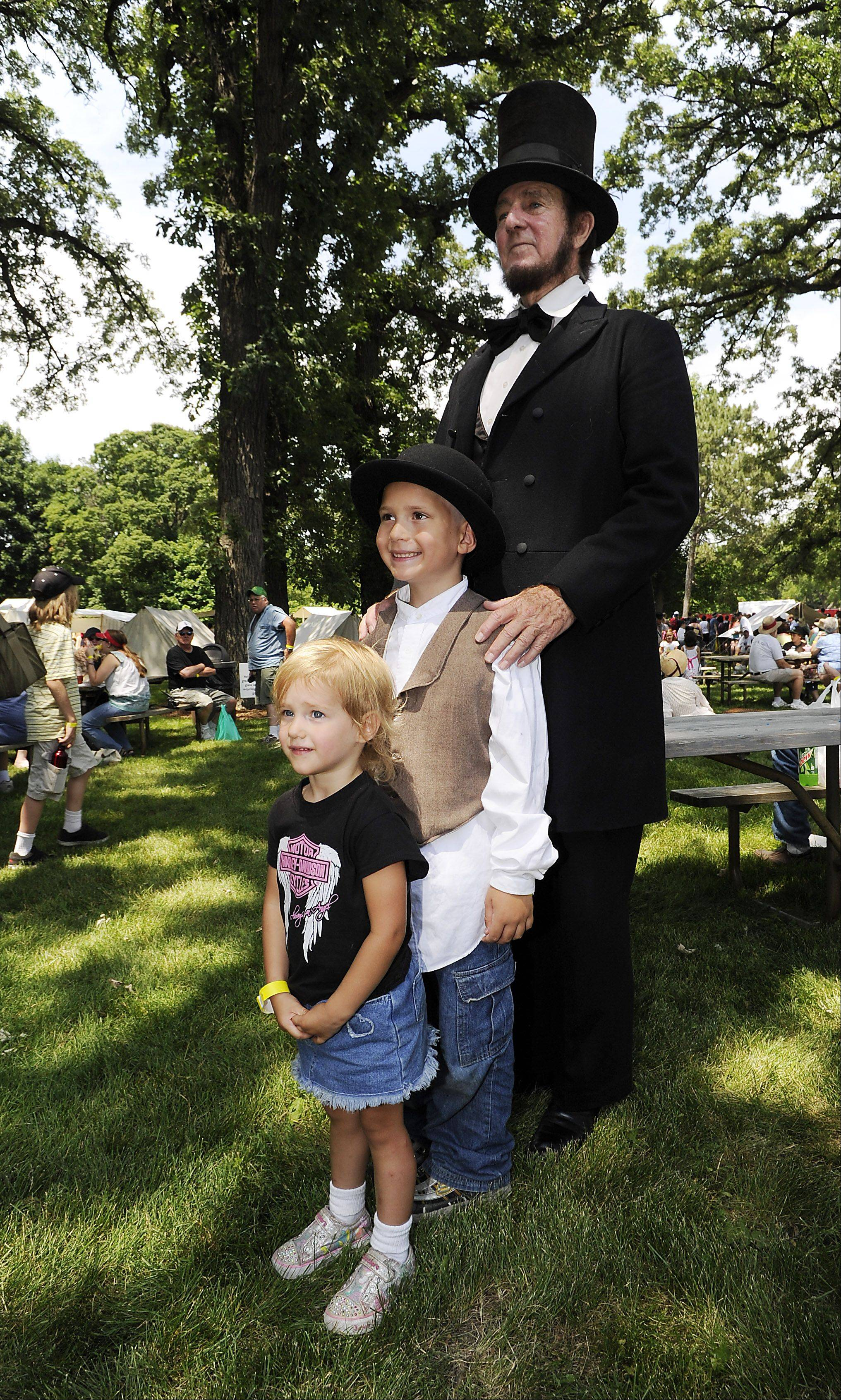 Standing tall is Max Daniels of Wheaton playing the character President Abraham Lincoln against some of his future voters Bailee Lizzo,3, of Third Lake and Wyatt Johnson,7, of Third Lake at the 20th annual Civil War days in the Lake County Forest Preserve on Saturday.