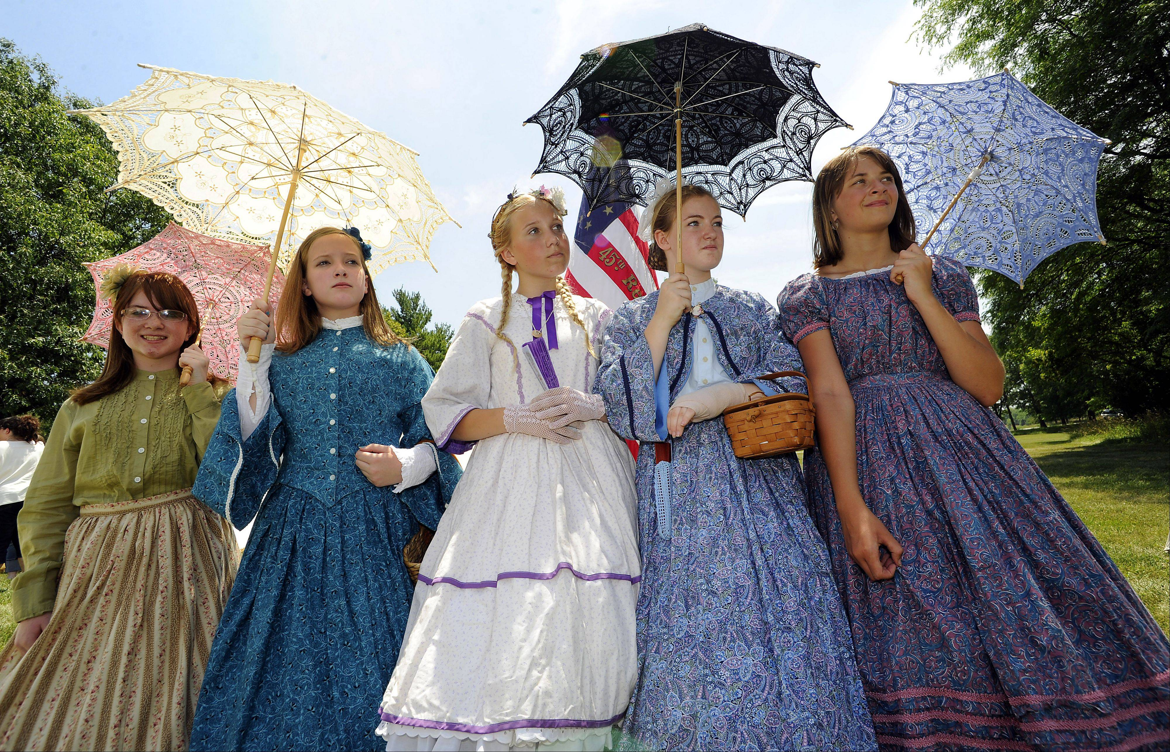 Civil War girls, Lauren,12, and Makena Haines,13, with TaylorAnne Stefanski,13, Libbie Barden,13, and Destiny Gorman,14, dressed in their hoop dresses watch over the events of the day at the 20th annual Civil War days at the Lake County Forest Preserve on Saturday.