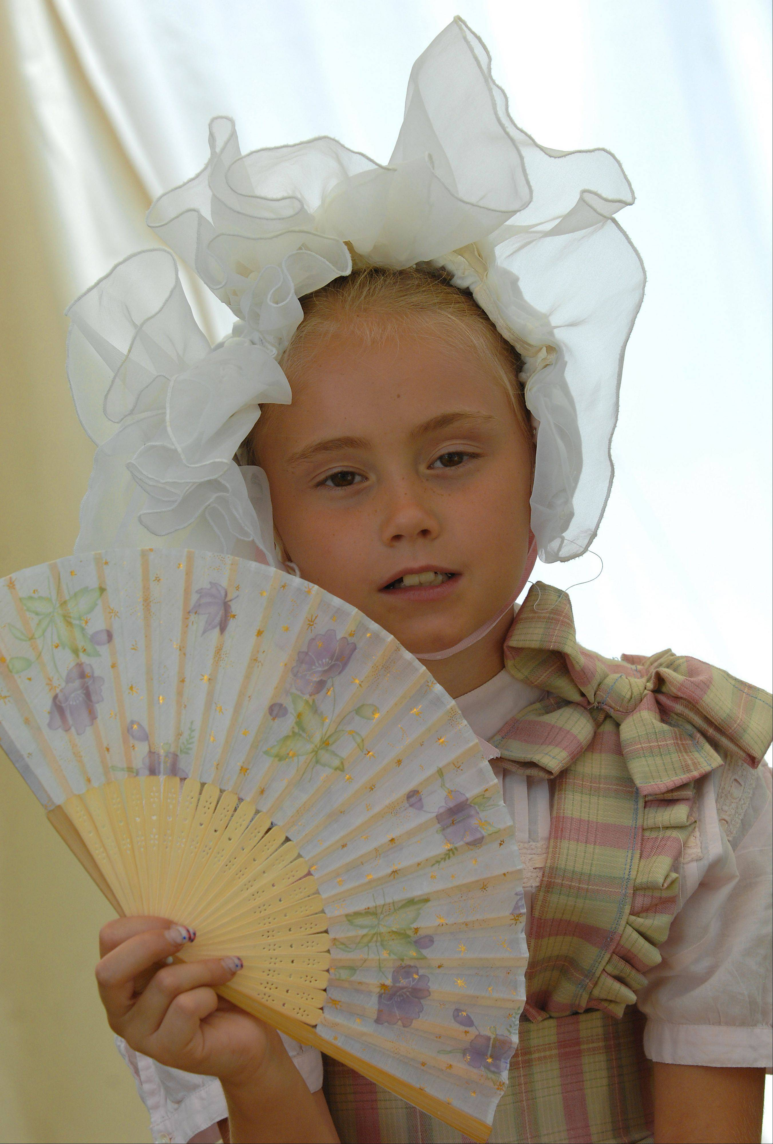 Lacey Schroeder,7, of Wisconsin uses her fan on a hot summer day to keep cool.