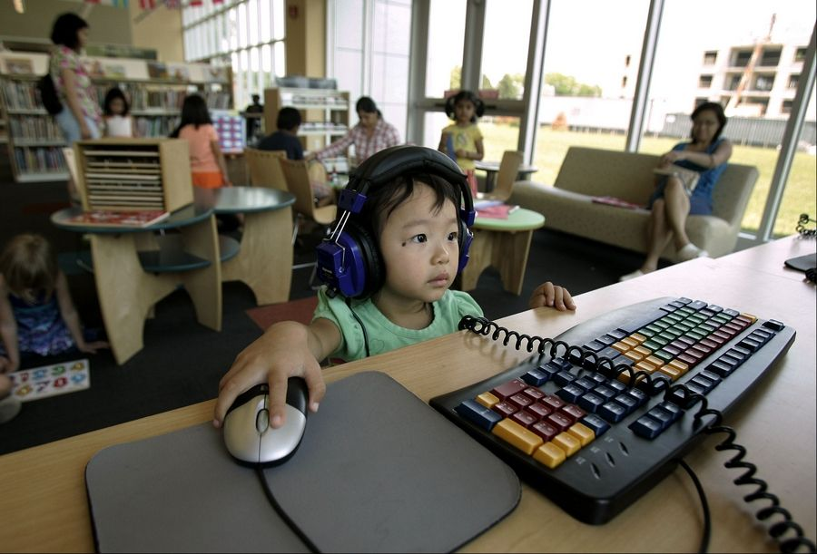 Yvonne Tarman, 2, of Libertyville plays on a computer in the children's section at the Aspen Drive Library in Vernon Hills.