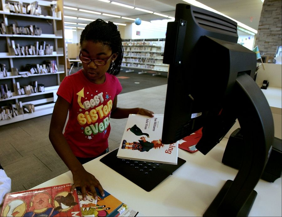 Laila Morgan, 7, of Vernon Hills checks out books at the Aspen Drive Library in Vernon Hills. Patrons borrowed more than 600,000 items during the facility's first 11 months of service, records show.
