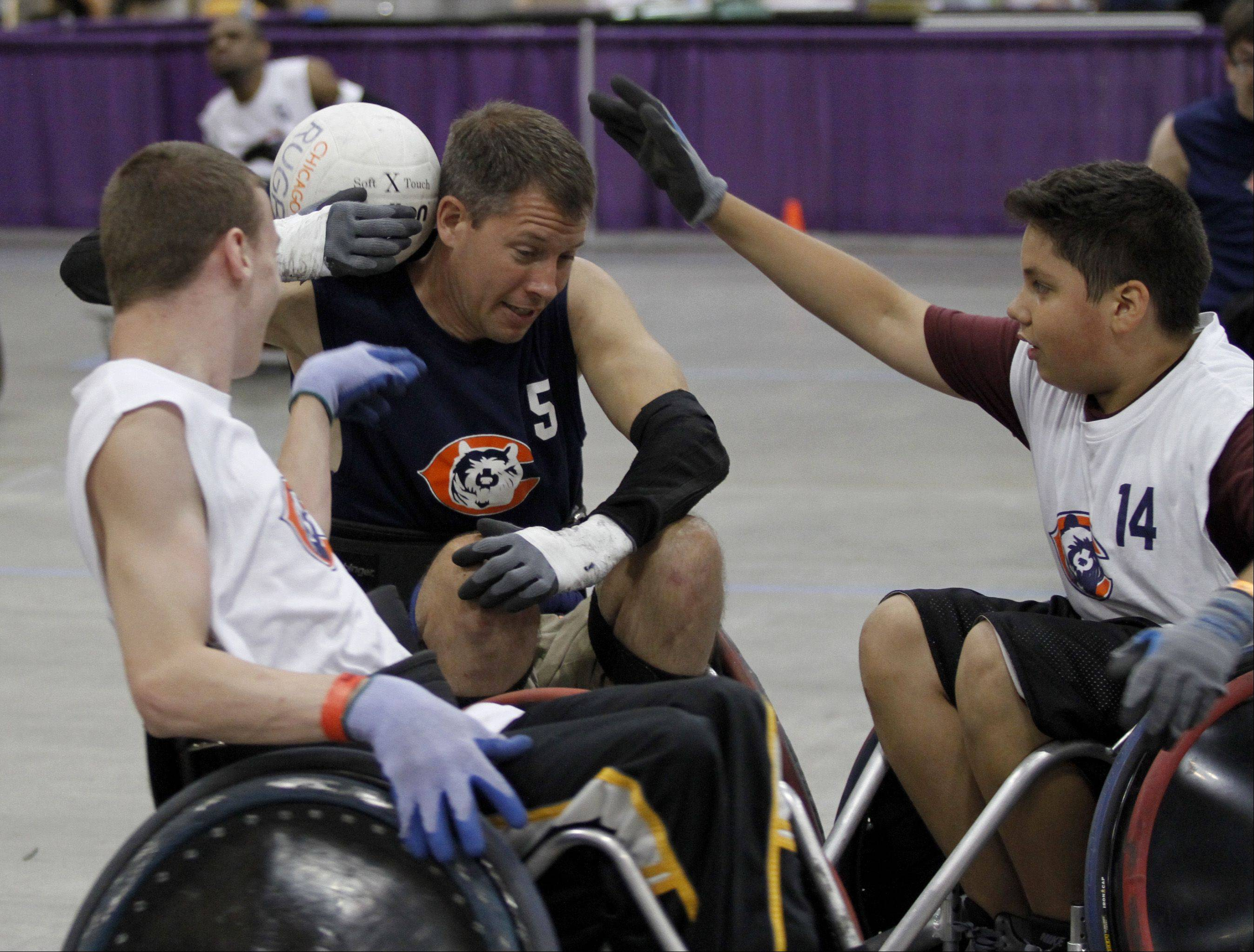 Dan Sauber, middle, tries to keep the ball away from opponents Matt Molenkamp, left, of Itasca, and Fernando Duarte, right, 13, of Cicero. The three are part of a wheelchair rugby team sponsored by the Rehab Institute of Chicago and the Chicago Bears.
