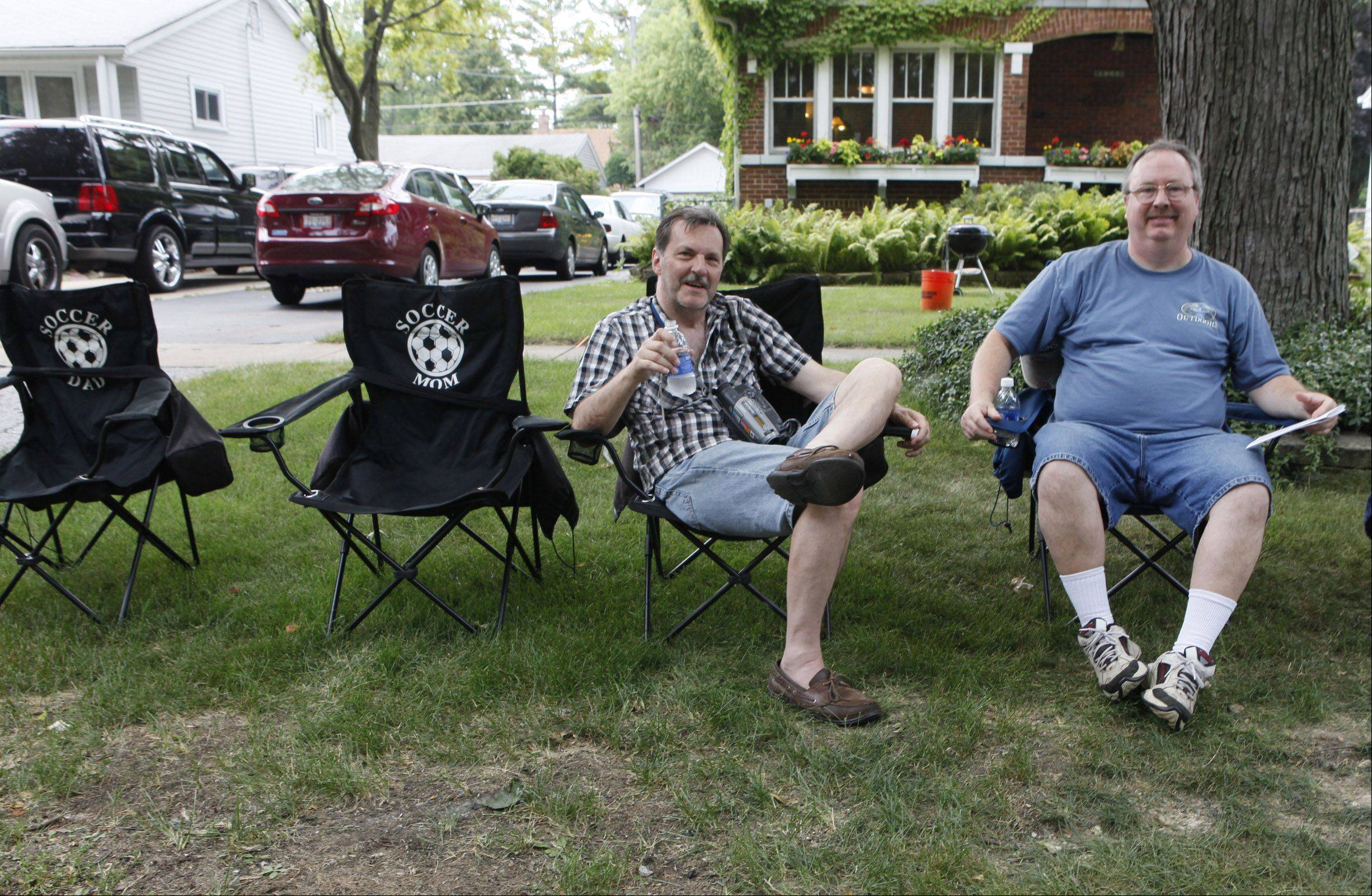 Still sitting after West Chicago's Railroad Days parade passed by Sunday, residents Rich Kassanits and Mark Patenaude relax in the shade on a hot summer day.