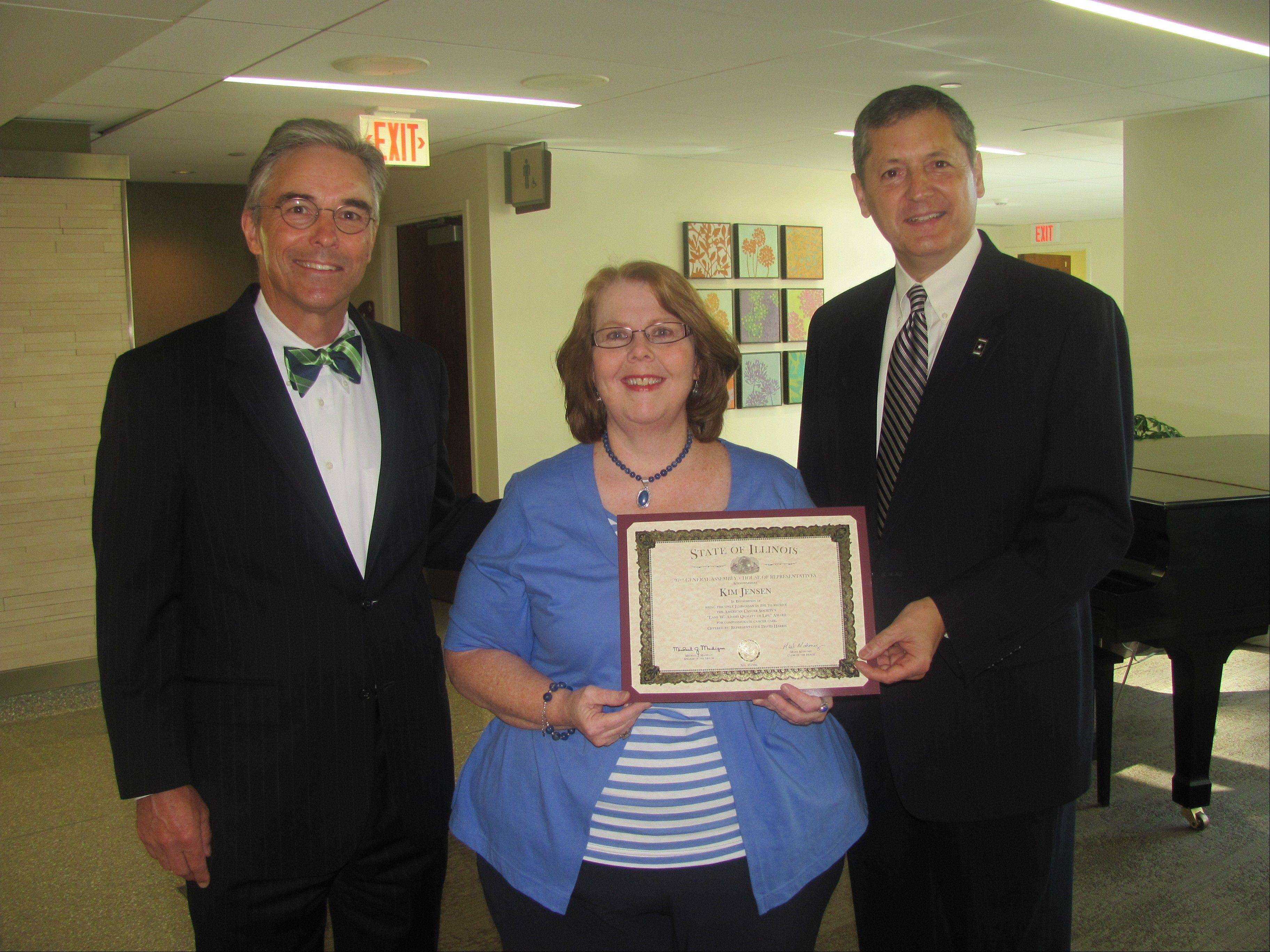 Kim Jensen, an oncology social worker at Northwest Community Hospital, receives congratulations from hospital President and CEO Bruce Crowther, left, and state Rep. David Harris. She was honored for her work with cancer patients and their families.