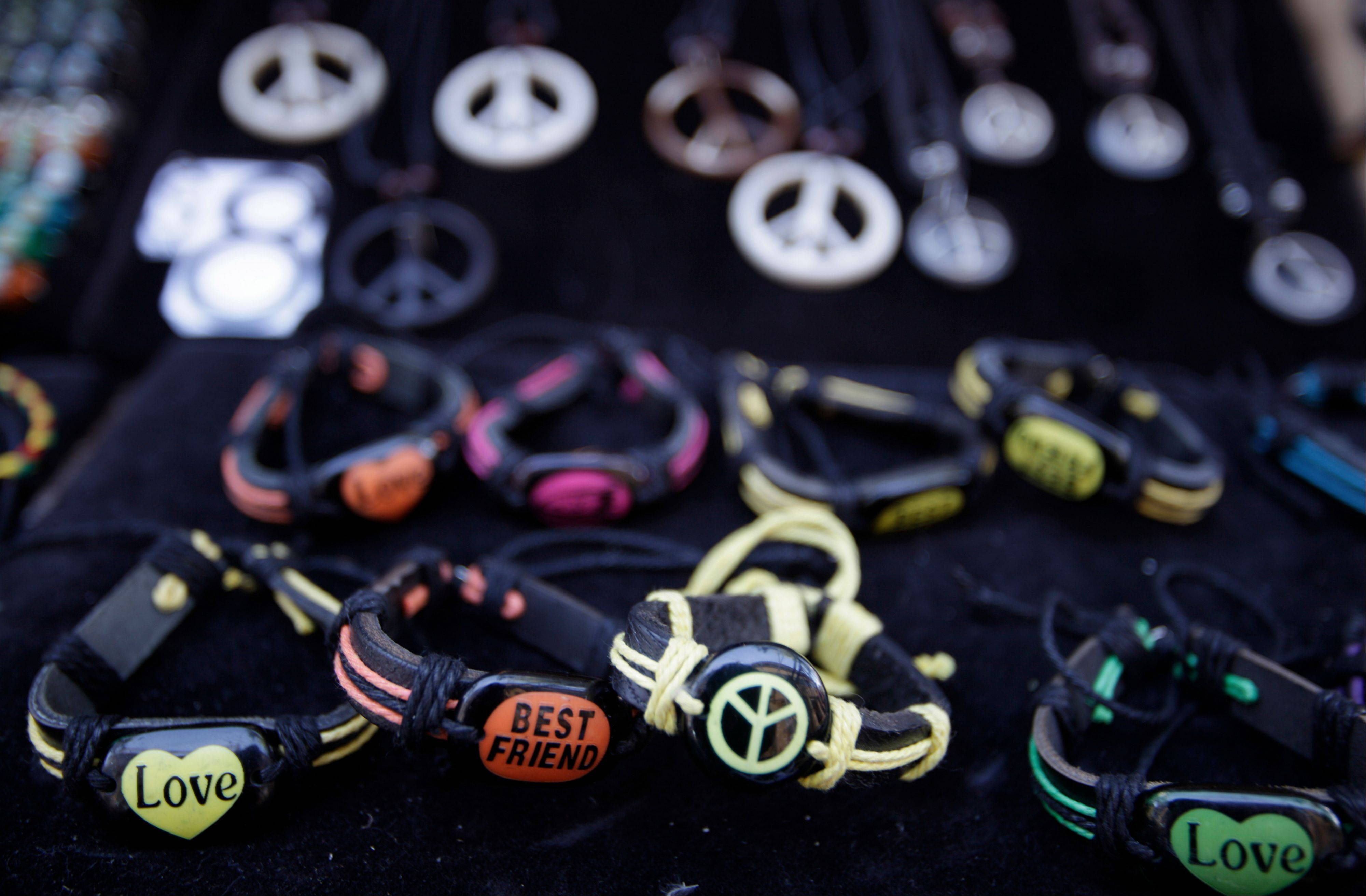 Necklaces and bracelets with peace signs are sold along the sidewalk on Telegraph Avenue in Berkeley, Calif.