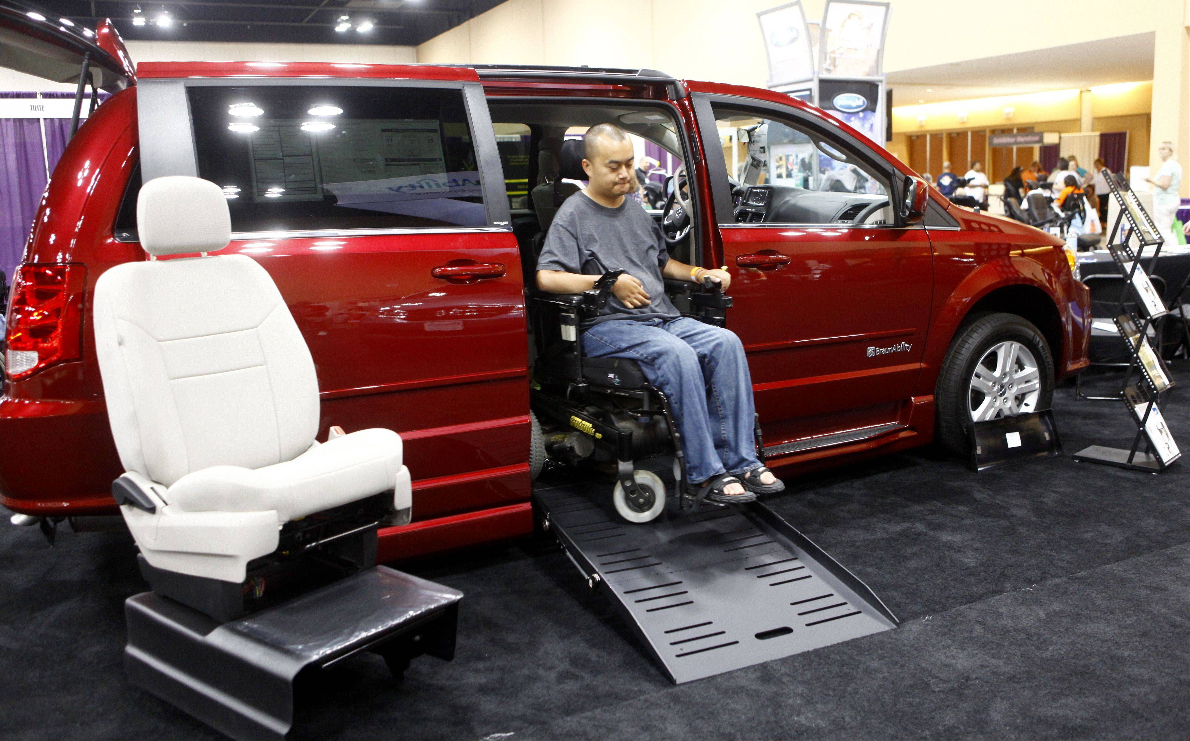 Blong Moua, of Madison, Wis, tries out one the many wheelchair accessible vans that were on display at the annual Abilities Expo on Sunday at the Schaumburg convention center.