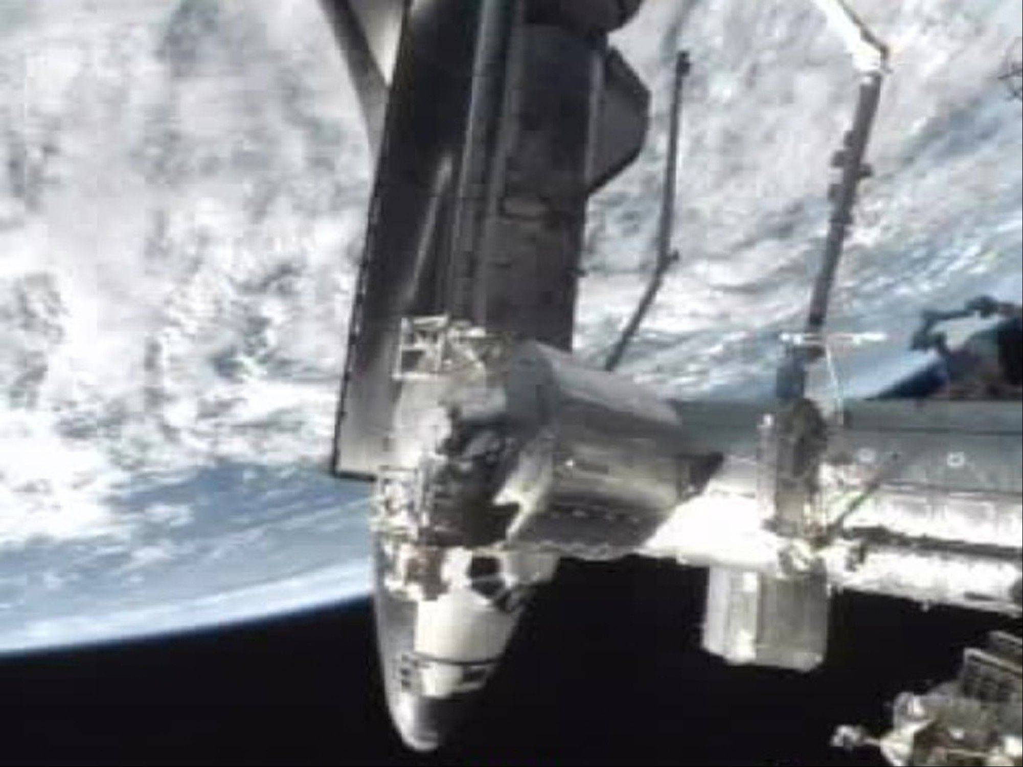 The shuttle Atlantis docks at the International Space Station on Sunday. Atlantis delivered more than 4 tons of food, clothes and other space station provisions.