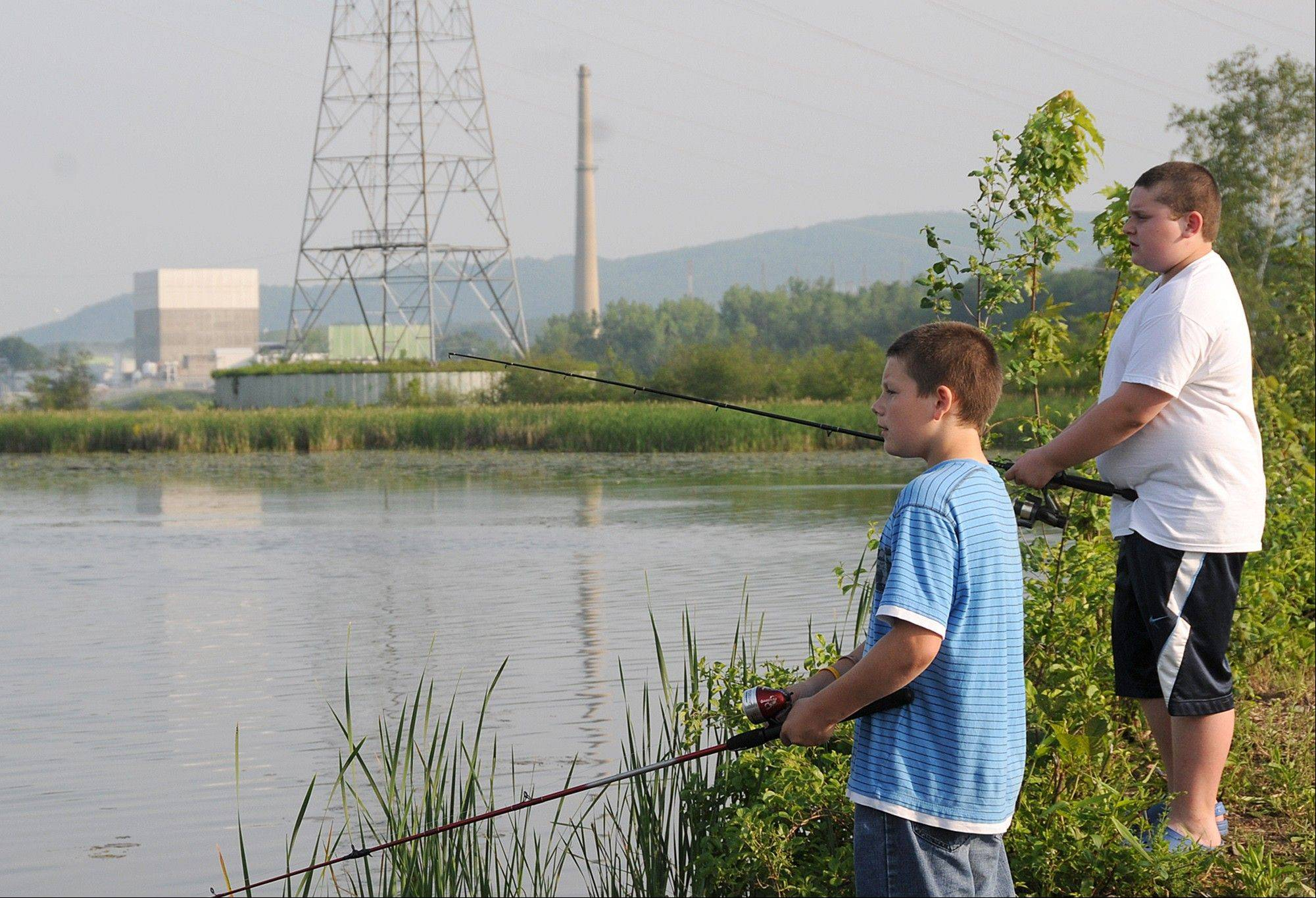 Two boys fish in the Connecticut River across from the Vermont Yankee nuclear power plant.
