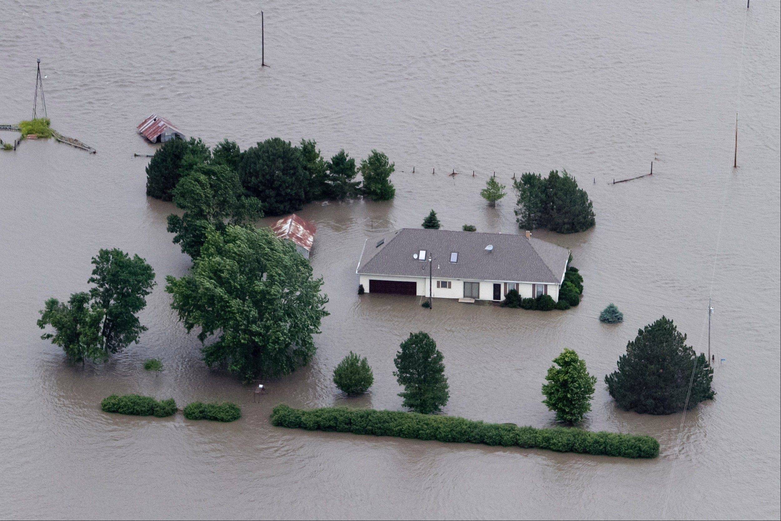 A home is engulfed by floodwater in Hamburg, Iowa, from the rising Missouri River. Insurance agents in states along the swollen Missouri River basin say federal officials are causing widespread confusion.