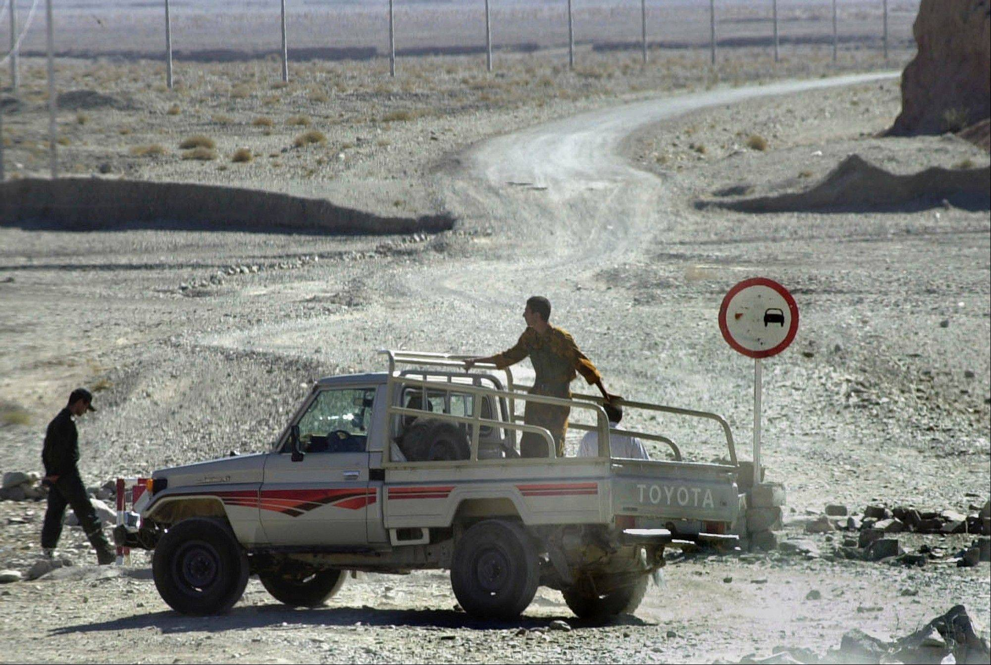 Iranian border guards watch for Afghan refugees on a road which leads to Afghanistan at the Ghargharook checkpoint on the Iran-Afghanistan border. A former Bush administration official told the AP in 2008 that Iran had rounded up hundreds of Arabs who had crossed the border from Afghanistan, expelled many of them and made copies of nearly 300 of their passports in an effort to help the U.S. counter al-Qaida after Sept. 11, 2001. It was a moment of rare common purpose between Iran and Washington that could have opened doors for greater diplomatic overtures.