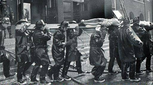 Detroit firemen carry a 13-foot crucifix from Our Lady of Sorrows Catholic Church on the city's east side after a five-alarm fire destroyed the church in 1963.