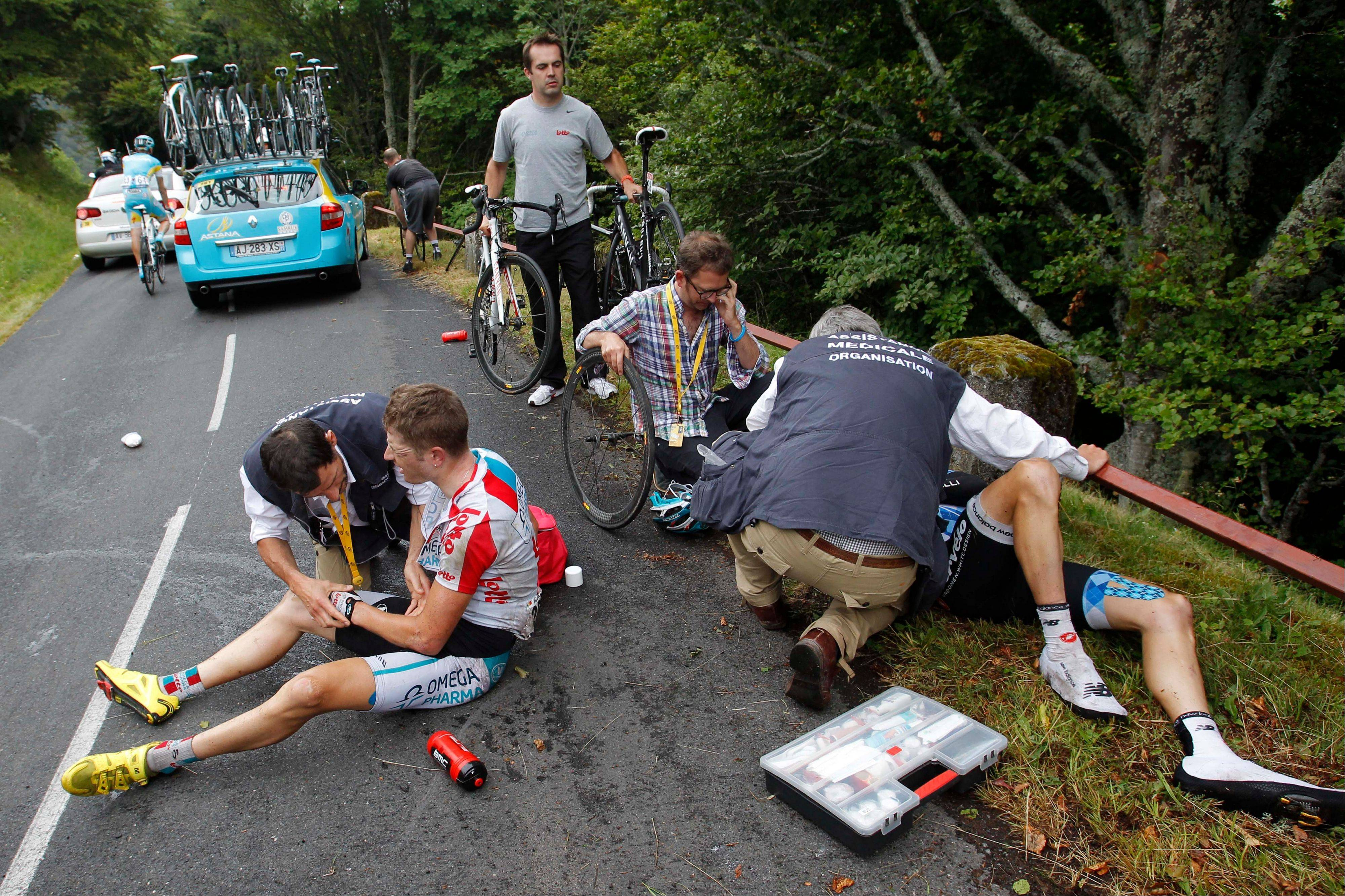 Frederik Willems of Belgium, left, and David Zabriskie of the U.S. get treatment after crashing during Sunday's 9th stage.