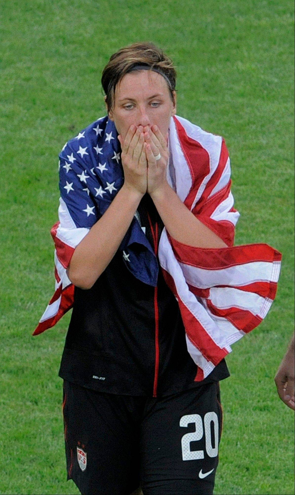Abby Wambach is wrapped in a U.S. flag after her team defeated Brazil in a penalty shootout.