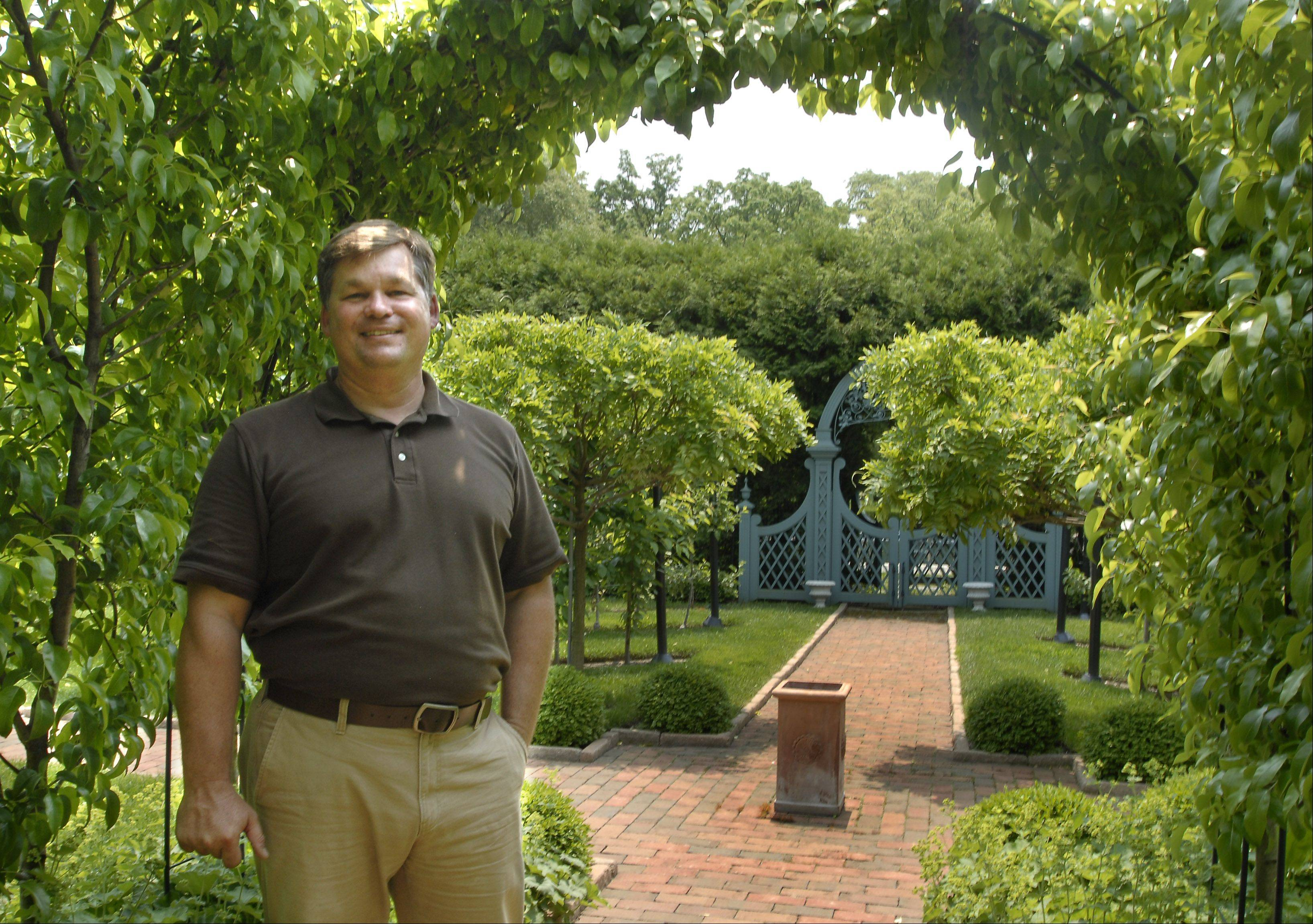 Landscape designer John Staab stands under an arch of pear trees in the Barrington Hills potager. The first work he did for Vicky and John Wauterlek on their 10 acres was in 1985 when he was an intern.
