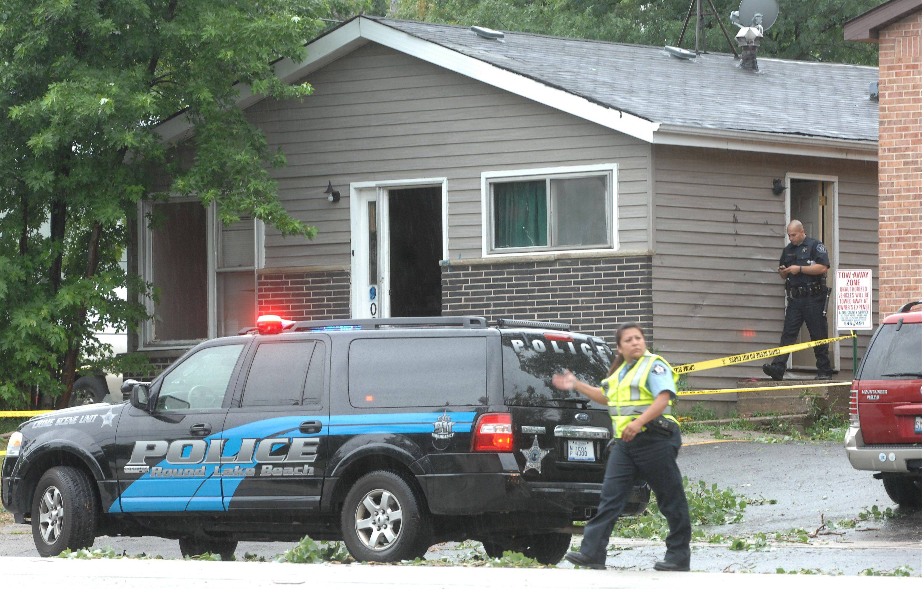 Police officials investigate the scene of a standoff Monday morning in the 900 block of Cedar Lake Road in Round Lake Beach.