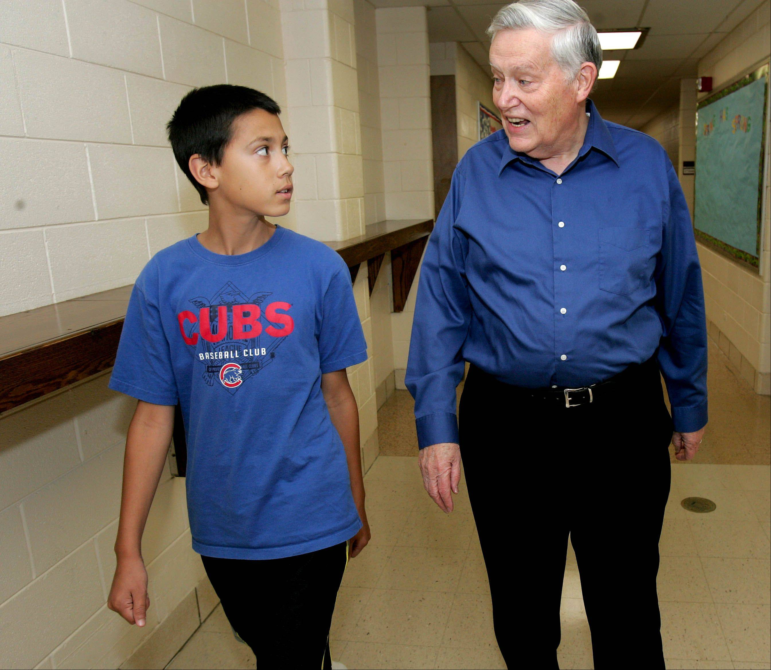 Ken Black of Roselle walks down the hall with Joey Sandoval, 12, at Trinity Lutheran Church in Roselle, where Joey is enrolled in summer camp. Joey�s mentor, Black, started the Adults Involved in Mentoring Students while working with the senior ministry at the church nine years ago. AIMS now serves students in five elementary districts, Lake Park High School District 108 and Trinity Lutheran School.