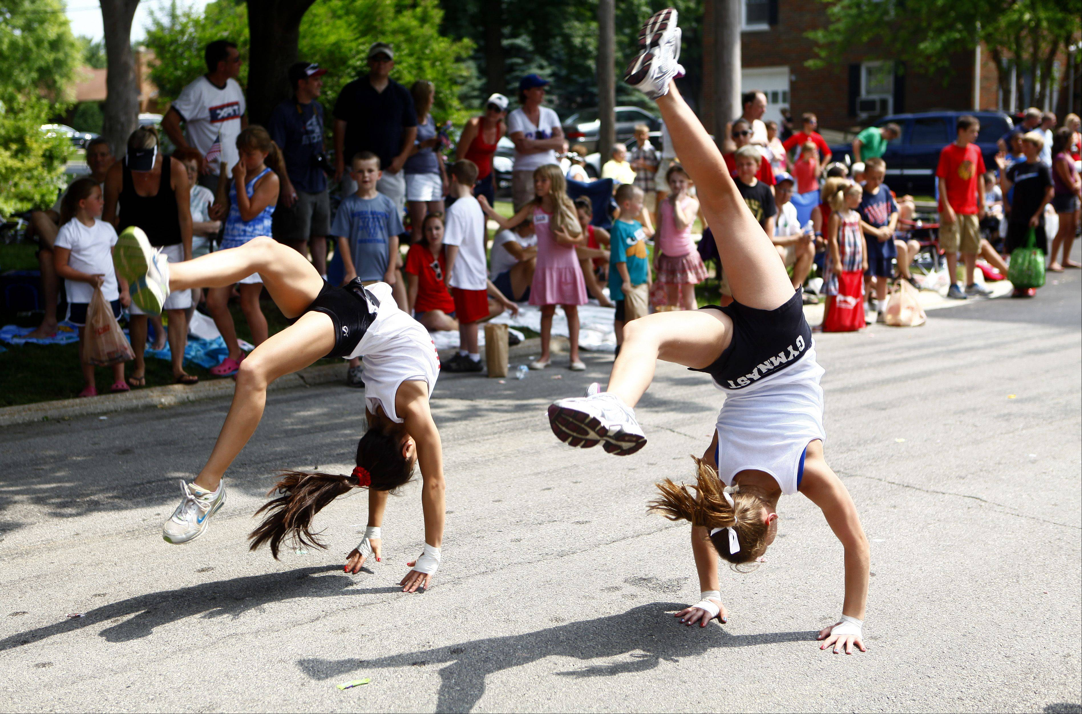 Anna Osowski, left, 12, from Barrington and Abby Moran, 11 from Rolling Meadows, perform a series of back flips for the crowd during the annual Palatine Jaycees Independence Day Parade Saturday morning.