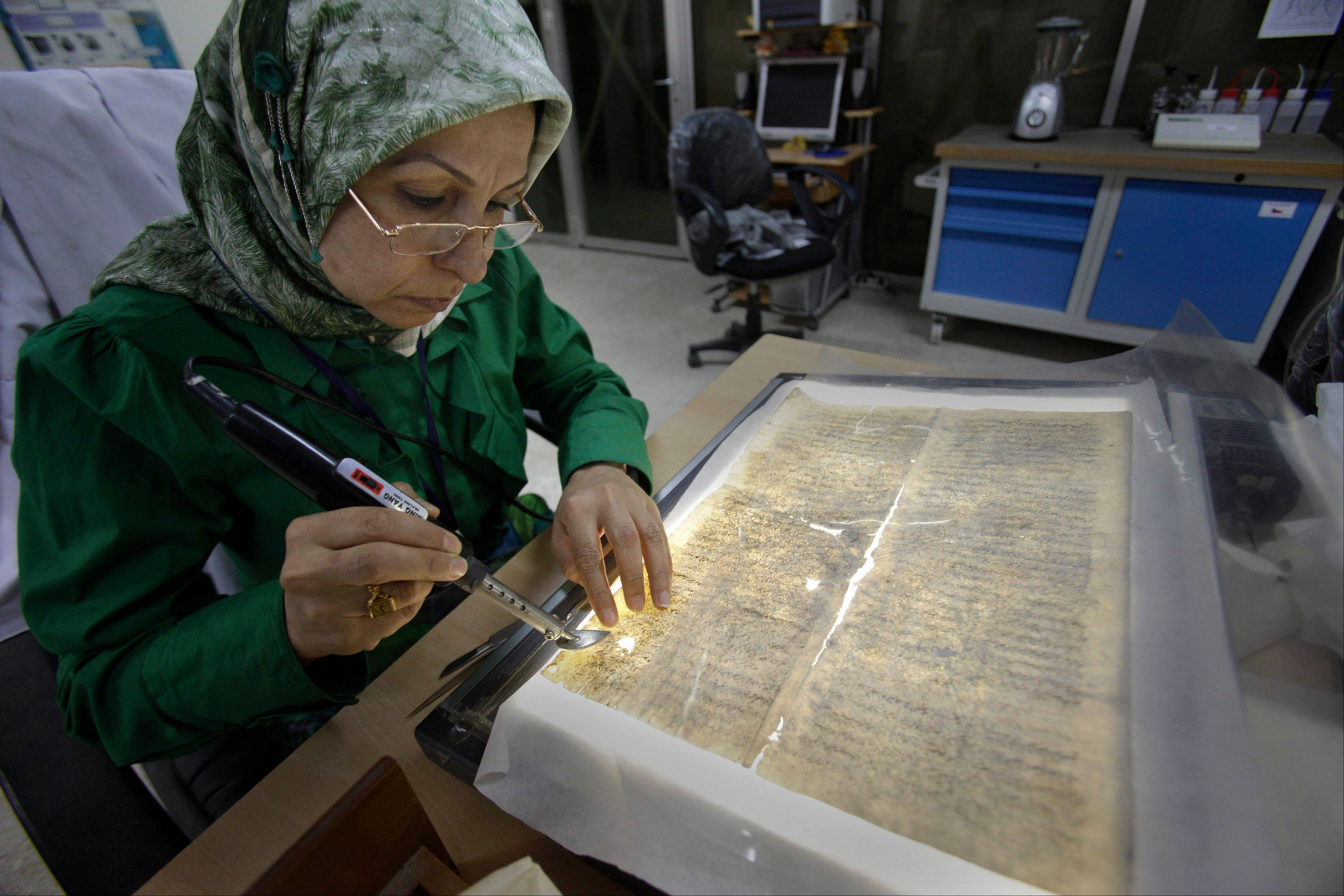 Alaa Jassim, a member of the library restoration staff, works on a damaged document at the Iraqi National Library in Baghdad.