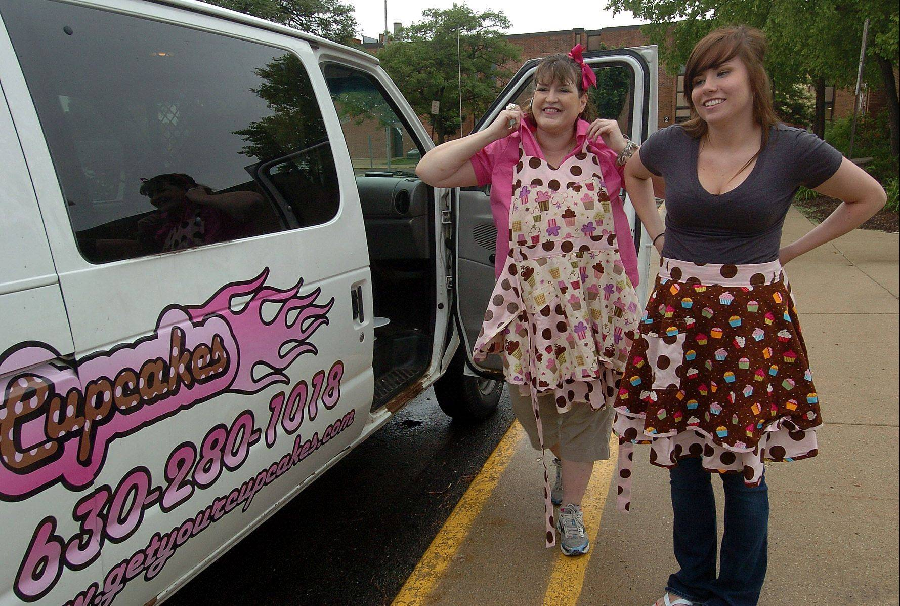 Angie DeFabis-Moeller, owner of Cruisin' Cupcakes, and her employee, Natalia Dabrowski, put on aprons before handing out samples to potential customers at a Schaumburg youth baseball game. DeFabis-Moeller says her cupcake truck has been wildly successful.