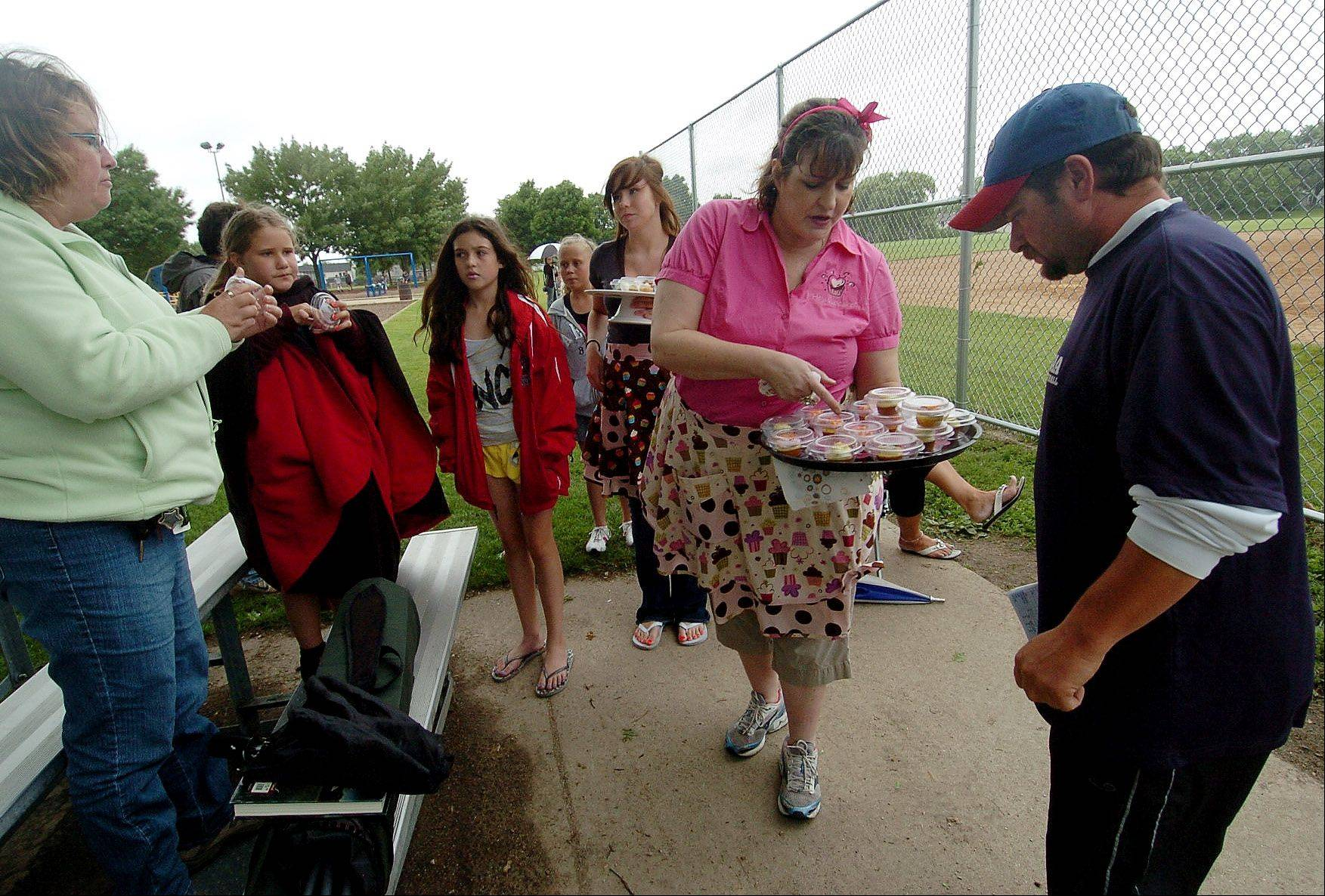 Angie DeFabis-Moeller, owner of Cruisin' Cupcakes, offers a cupcake to coach Steve Geotsalitis of the Schaumburg Athletic Association Jayhawks.
