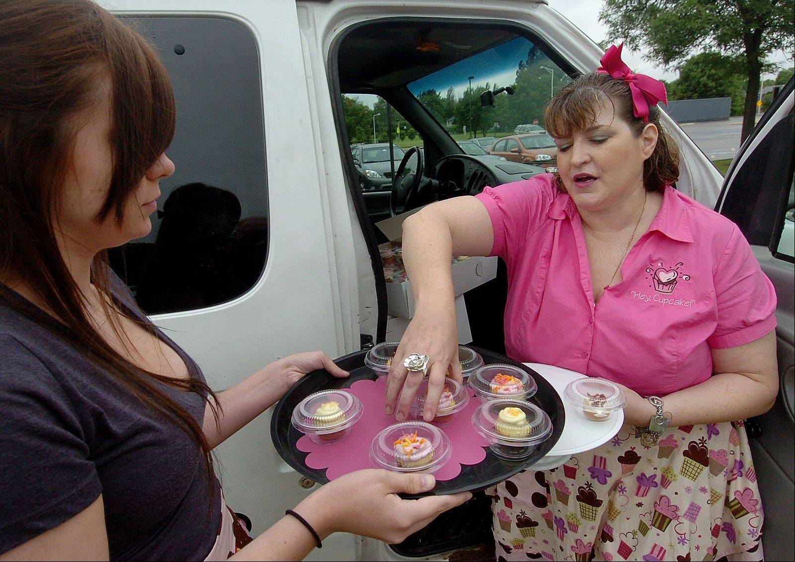 Angie DeFabis-Moeller, owner of the Schaumburg-based Cruisin' Cupcakes food truck, and her employee, Natalia Dabrowski, get free samples ready to hand out during a recent Schaumburg youth baseball game.