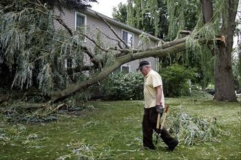 Del Rogers cleans up branches around his home on the corner of Crane and Dawes streets in Libertyville Monday morning after a dangerous thunderstorm blew through the area. The willow