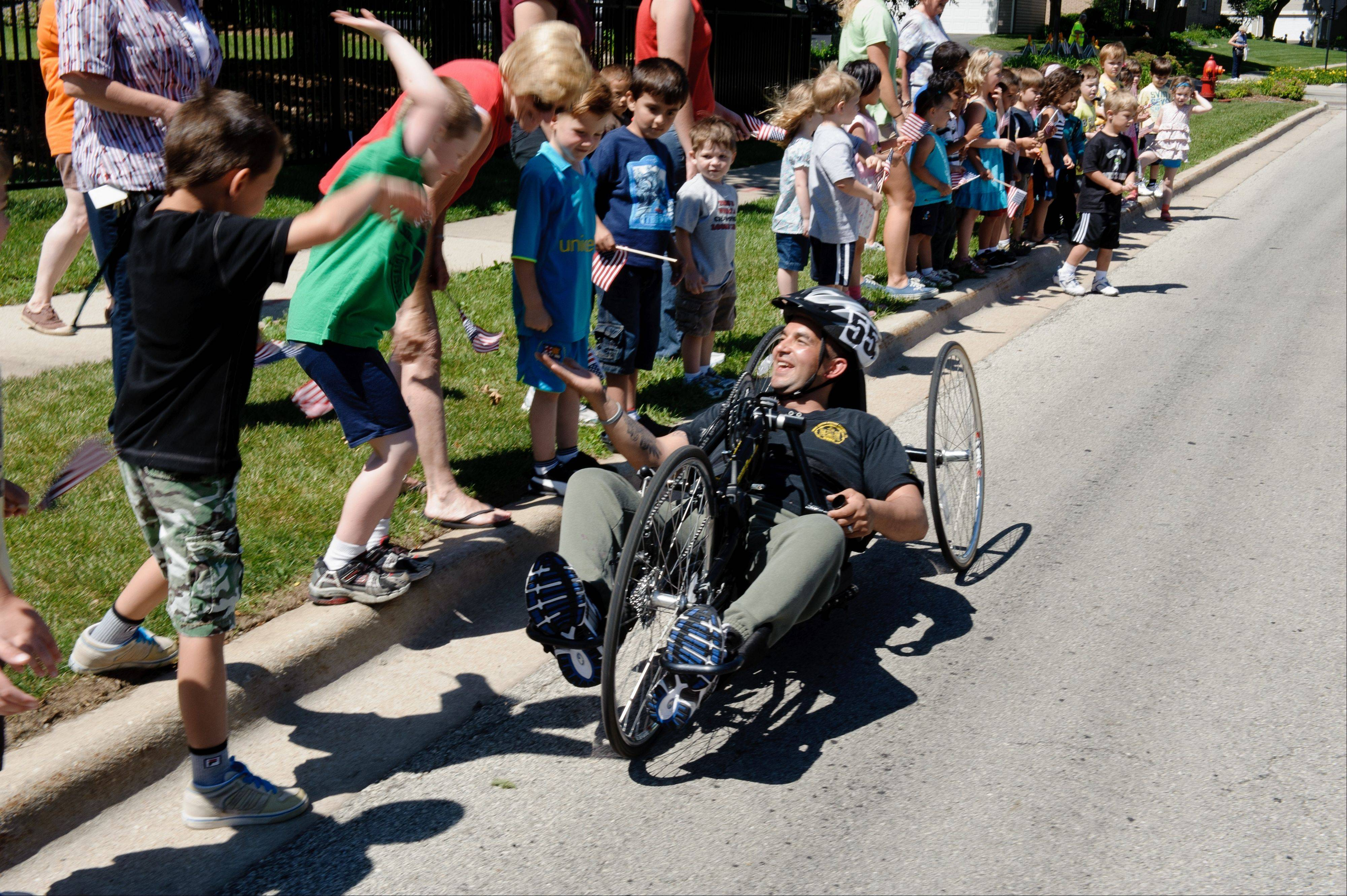"A veteran rides past cheering schoolchildren from the Hattendorf Center Day Care during the Heart Of a Marine Foundation's ""Meet the Athlete"" media day event Tuesday, June 28."