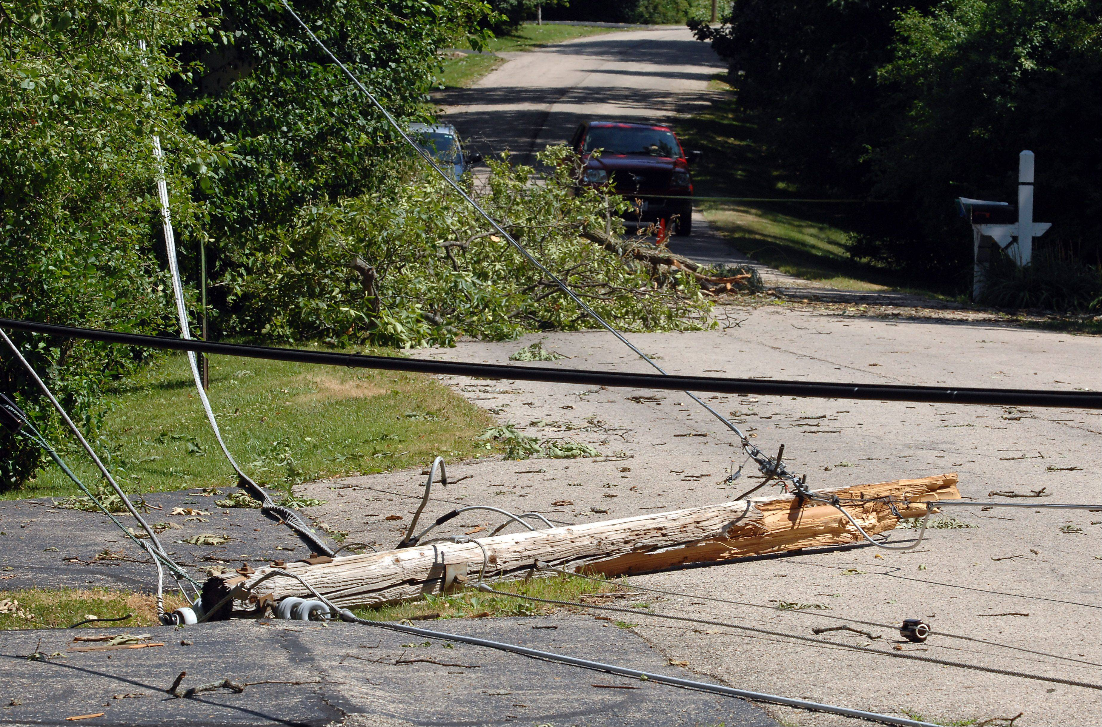 Utility poles lie with its wires crisscrossing Oakwood street in Barrington after Monday morning storm did a number on the area.