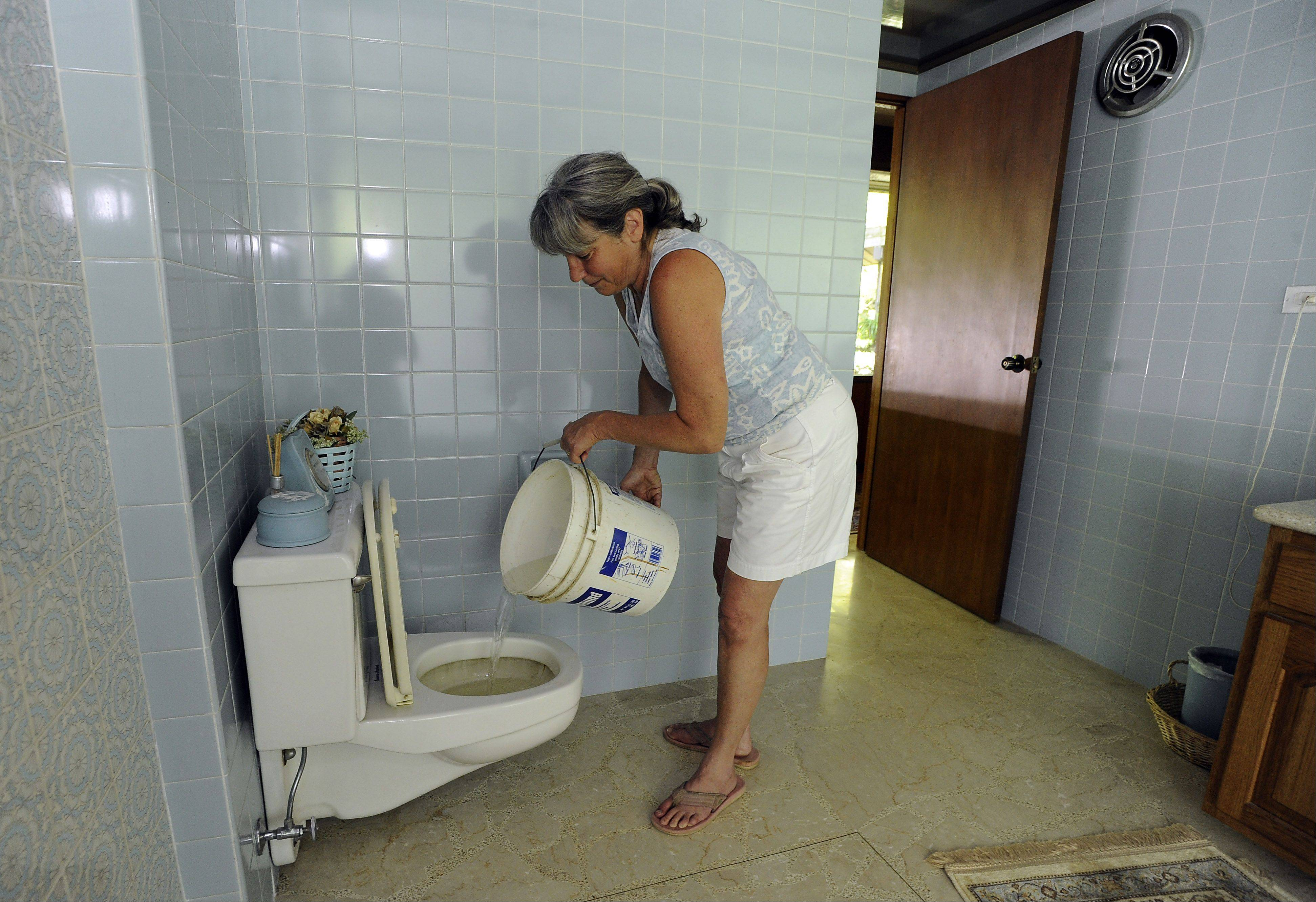 Wendy Schultz of Wisconsin who was helping out her Barrington parents Richard and Rosemary Libby who were hit hard by the storm has to pour well water into their toilets that she gets from her neighbor in order to use them.