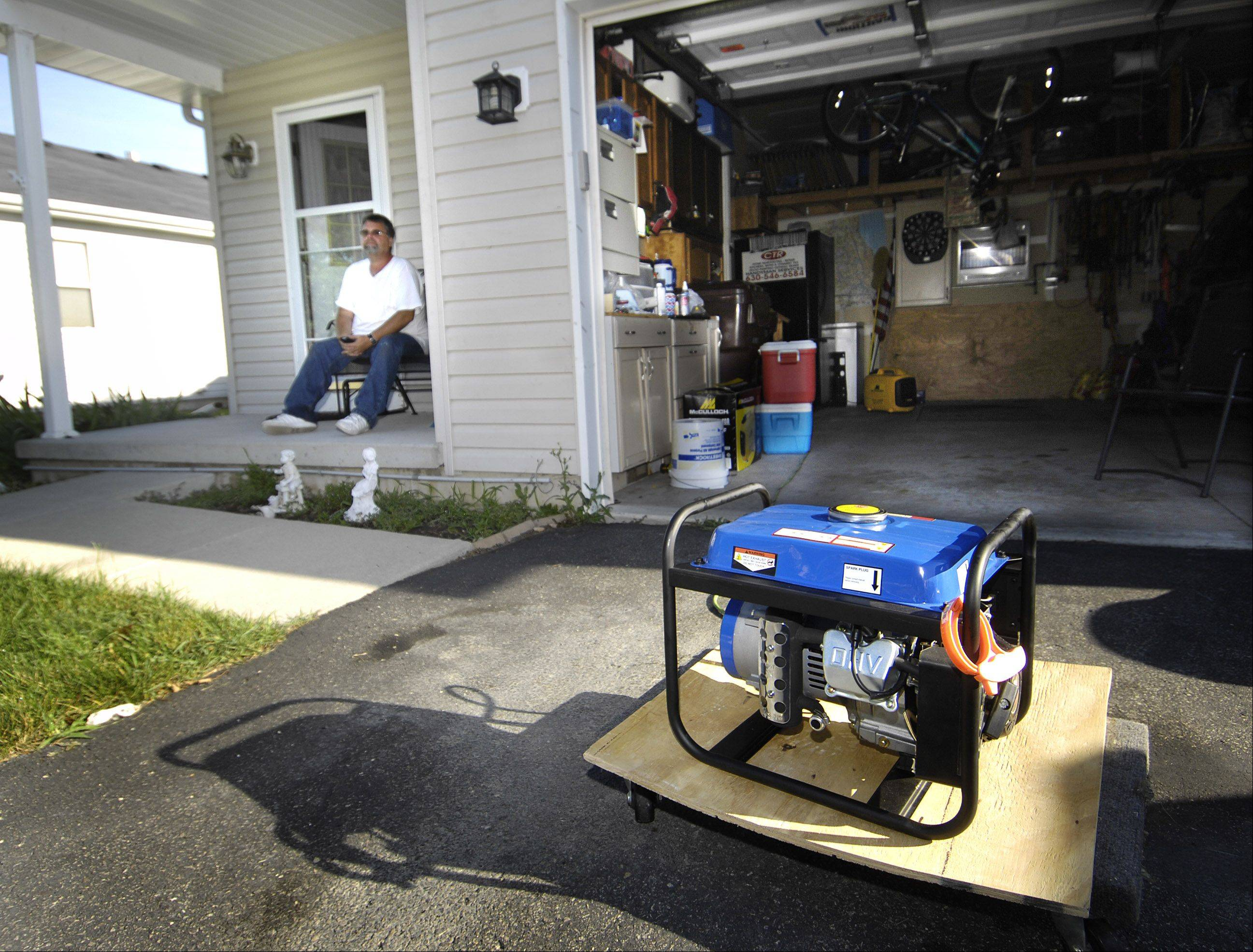 "Paul Ruiz sits on his Thornwood Lane porch with a generator running in his driveway Tuesday morning while waiting for power to be restored to his home on the west side of Crystal Lake. He said he could actually see the wind Monday morning. ""I've never seen anything like it."" Many of his neighbors are sharing generators."