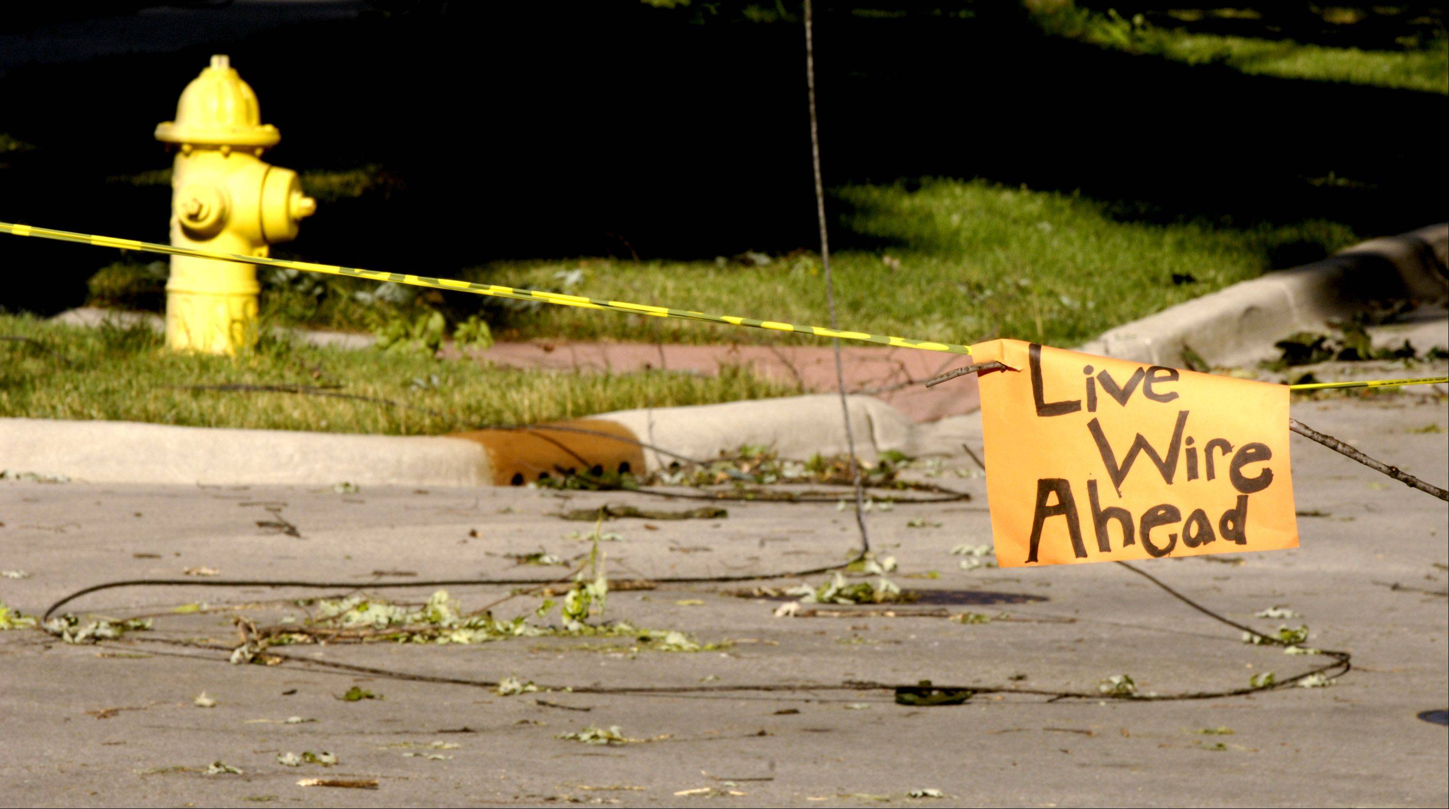 A hand made sign warns of downed wires at the intersection of Hillside and Forest Ave in Glen Ellyn. The wires are still on the ground nearly 24 hours after high winds blew through the Chicago area.