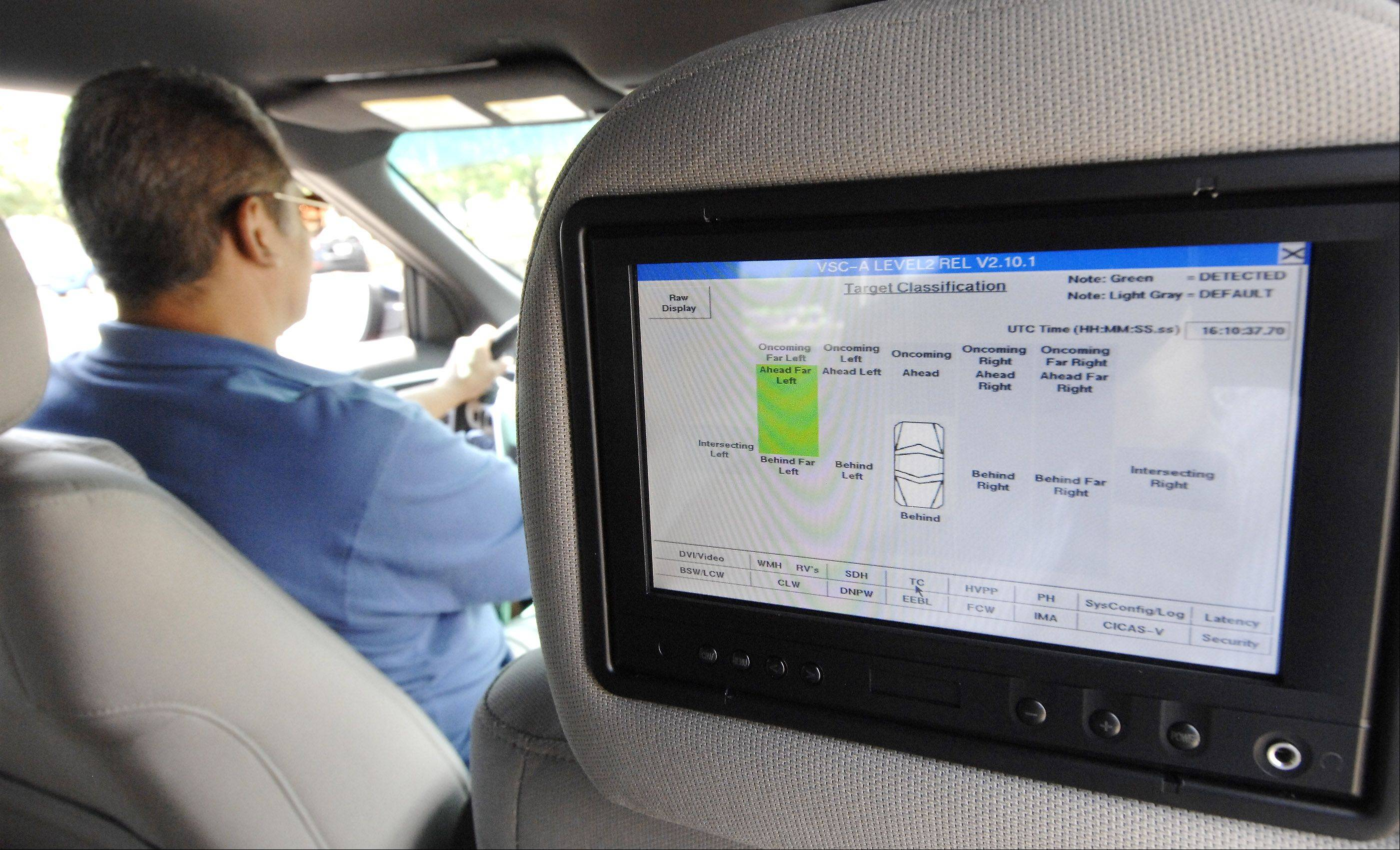 A demonstration display inside a prototype Ford intelligent vehicle Wednesday in Lombard shows how the system lights up in green to warn the driver of another car to the left.