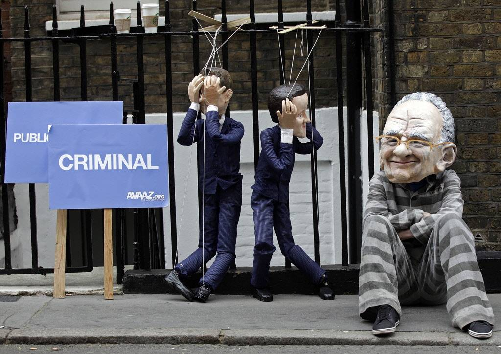 A demonstrator wears a mask depicting Rupert Murdoch, chief executive officer of News Corp., next to puppets of U.K. political figures during a protest outside Murdoch's apartment in London, U.K., on Wednesday
