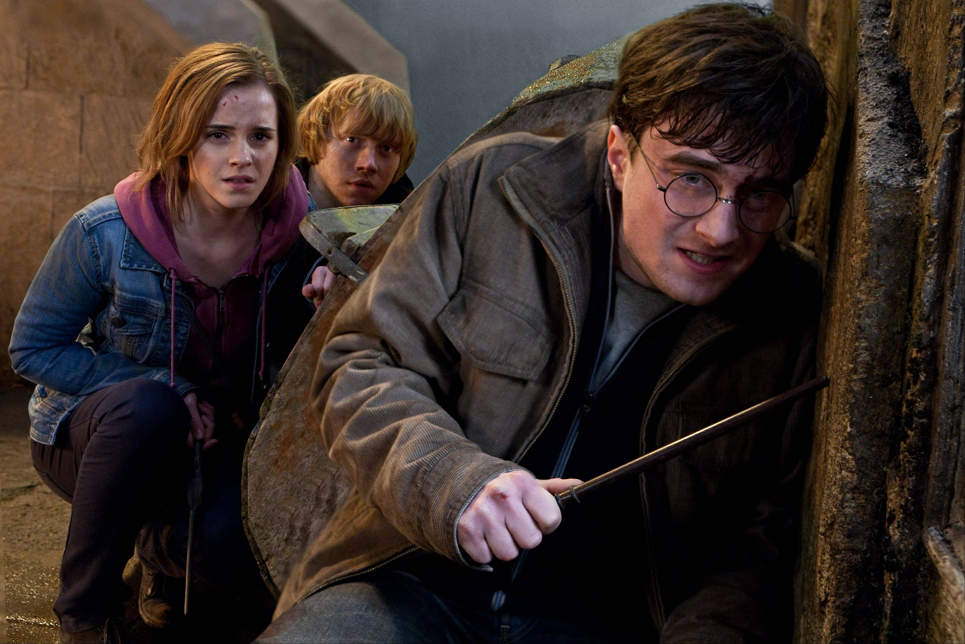 "Harry (Daniel Radcliffe), right, leads his pals Hermione (Emma Watson) and Ron (Rupert Grint) through a perilous battleground during ""Harry Potter and the Deathly Hallows -- Part 2."""