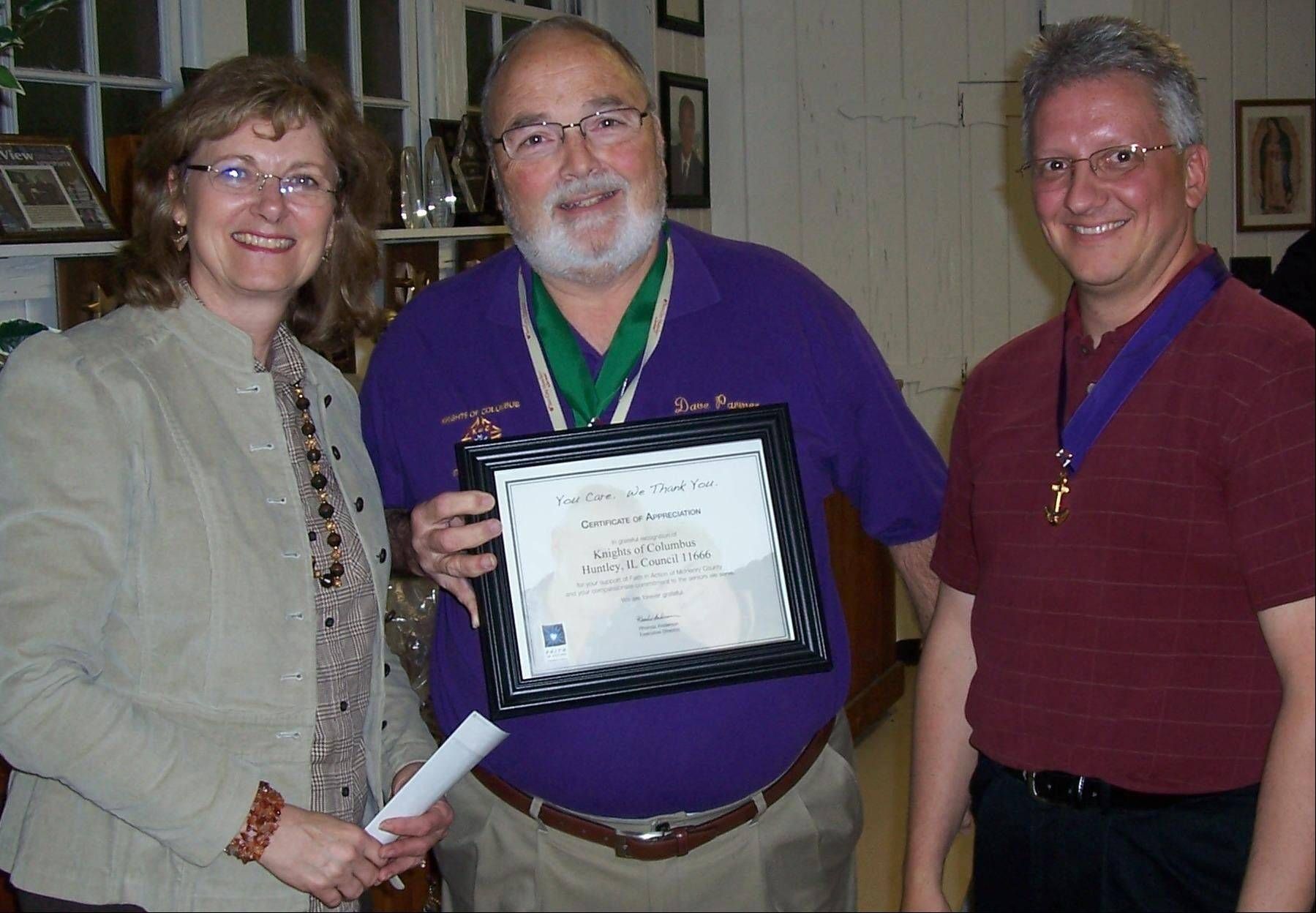 Rhonda Anderson, left, executive director of Faith in Action of McHenry County, presents a certificate of appreciation to Dave Parmer and Don Walz, right, of St. Mary of Huntley Knights of Columbus Council 11666 at the May meeting.