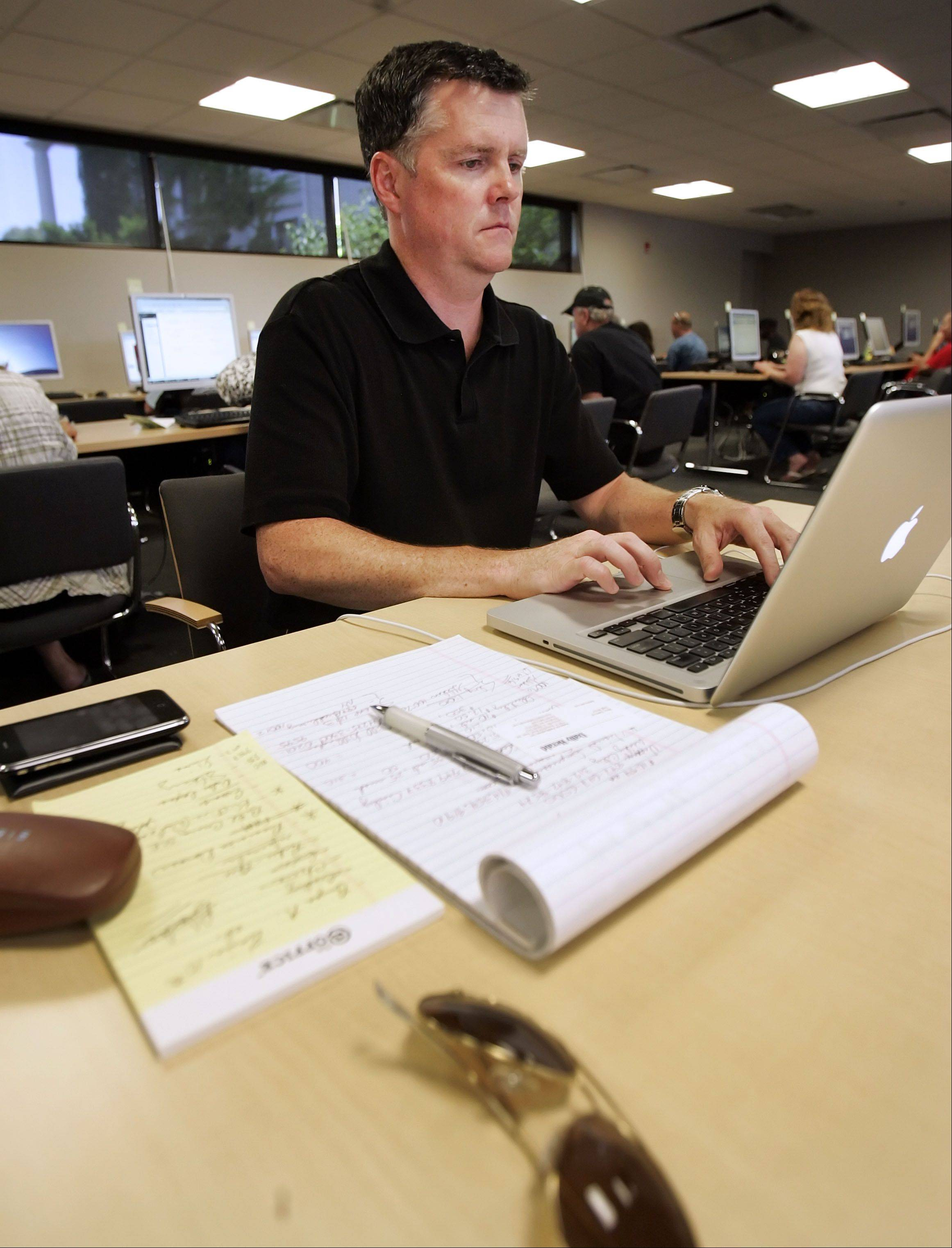 Businessman Parker Melvin of McHenry takes advantage of free Wi-Fi at Cook Memorial Public Library in Libertville Tuesday. Melvin is without power and is working out of the library after thunderstorms left hundreds of thousands of people without power.