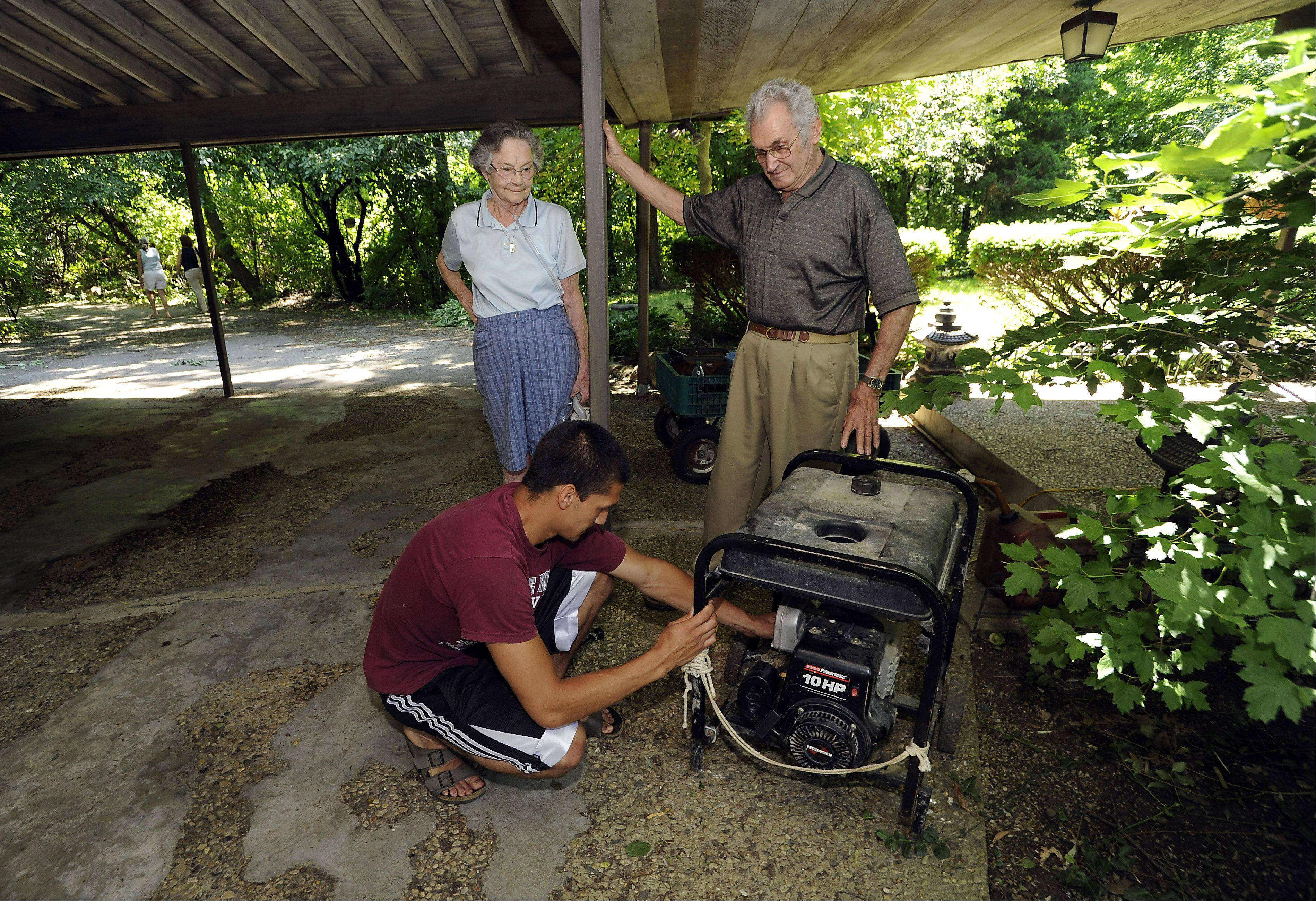 Lucas Zamudio, 20, of Barrington, fires up a generator Tuesday for his grandparents, Rosemary and Richard Libby of Barrington, who've been without power since Monday.