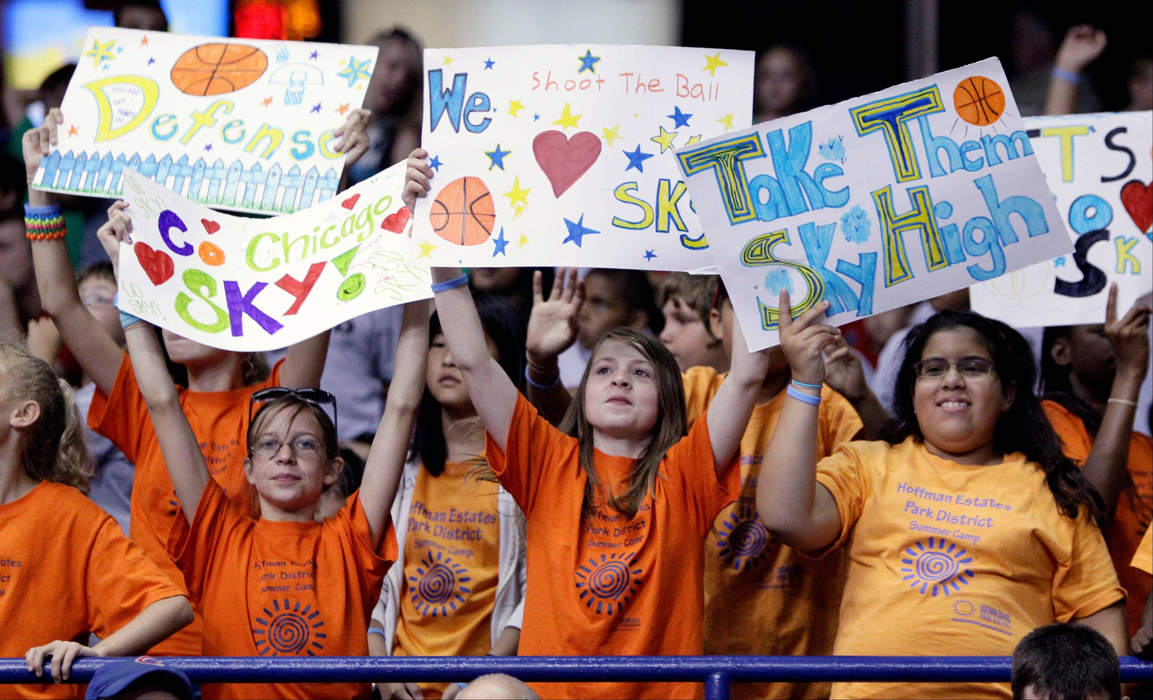 Fans hold signs as they watch the Chicago Sky battle the Tulsa Shock at the Allstate Arena on Wednesday.