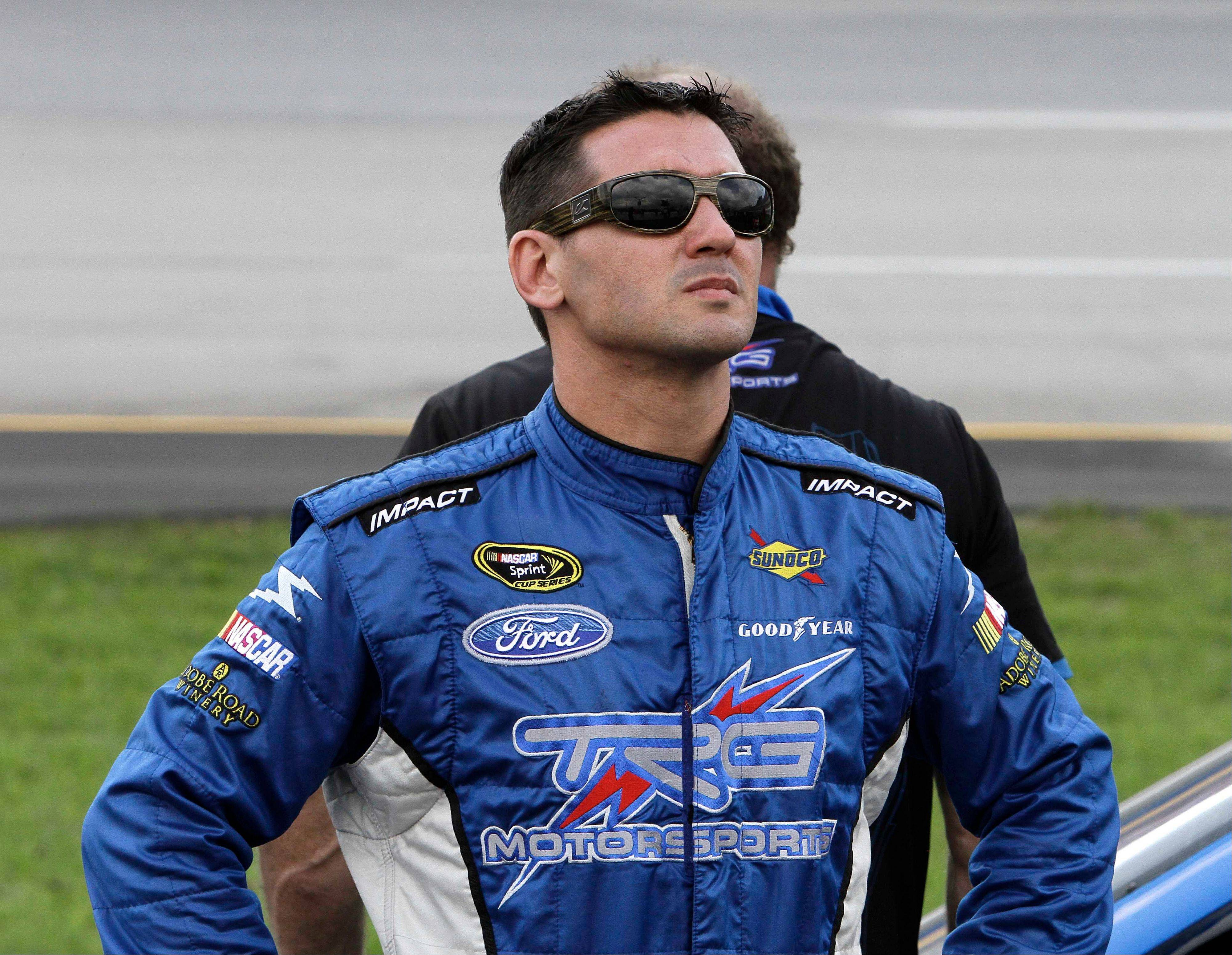 Andy Lally looks to the sky Friday as rain closes in on qualifying for the NASCAR Sprint Cup Series auto race at the Kentucky Speedway.