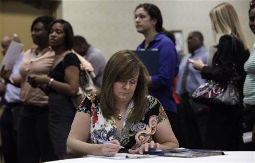 Cindy Bliss of Plano, Texas, fills out a questionnaire at a EFG Companies recruiting booth during a National Career Fairs job fair Wednesday in Dallas.